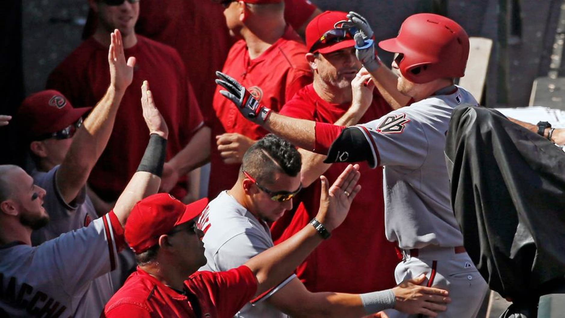 Arizona Diamondbacks' Phil Gosselin is congratulated by teammates as he enters the dugout after hitting a three run home run off the Colorado Rockies during the seventh inning of the first game of a baseball double header Tuesday, Sept. 1, 2015, in Denver. (AP Photo/Jack Dempsey)