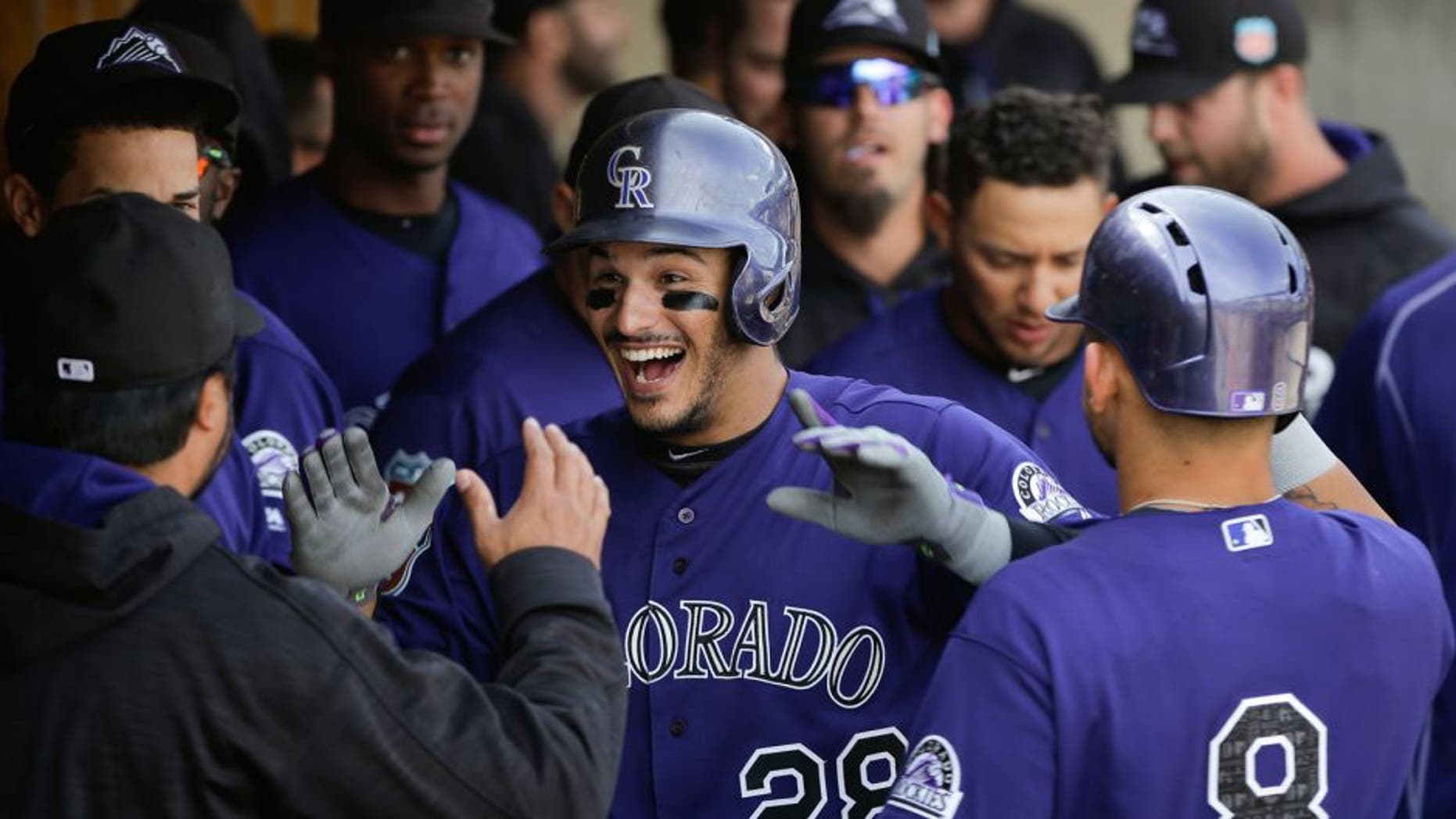Colorado Rockies' Nolan Arenado, center, is congratulated in the dugout after hitting his second home run of the game during the fifth inning of a spring training baseball game against the Arizona Diamondbacks Tuesday, March 29, 2016, in Scottsdale, Ariz. (AP Photo/Jae C. Hong)
