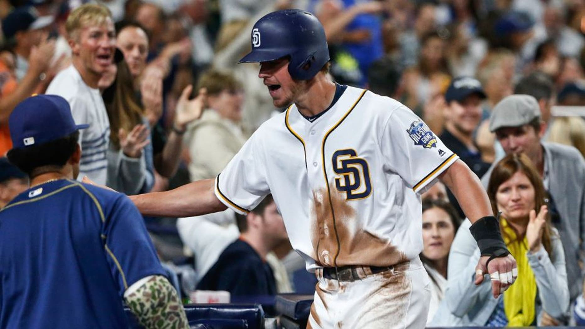 San Diego Padres' Wil Myers is congratulated at the dugout after scoring against the New York Yankees during the sixth inning of a baseball game Saturday, July 2, 2016, in San Diego. (AP Photo/Lenny Ignelzi)