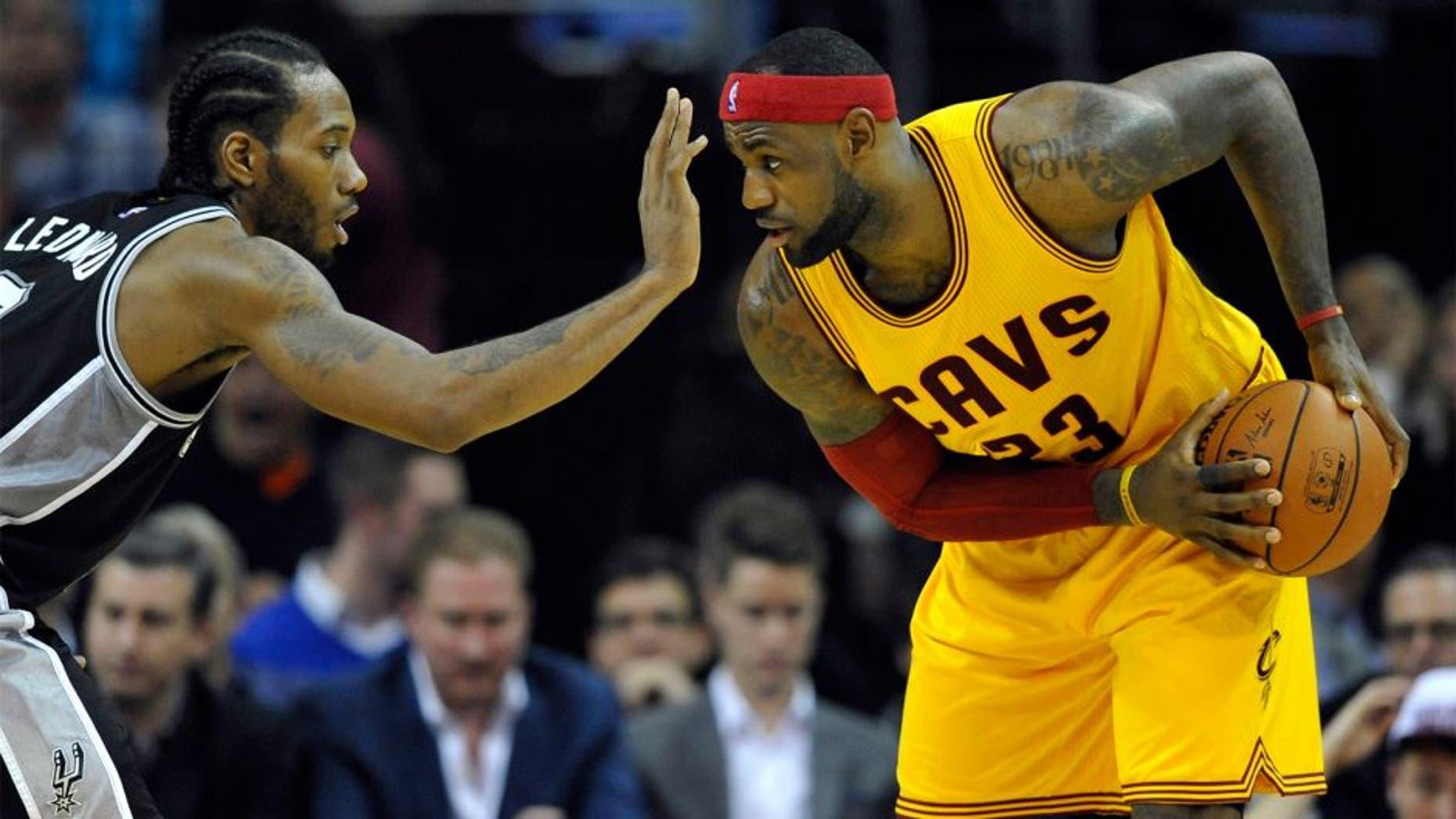 Nov 19, 2014; Cleveland, OH, USA; San Antonio Spurs forward Kawhi Leonard (2) defends Cleveland Cavaliers forward LeBron James (23) in the third quarter at Quicken Loans Arena. Mandatory Credit: David Richard-USA TODAY Sports