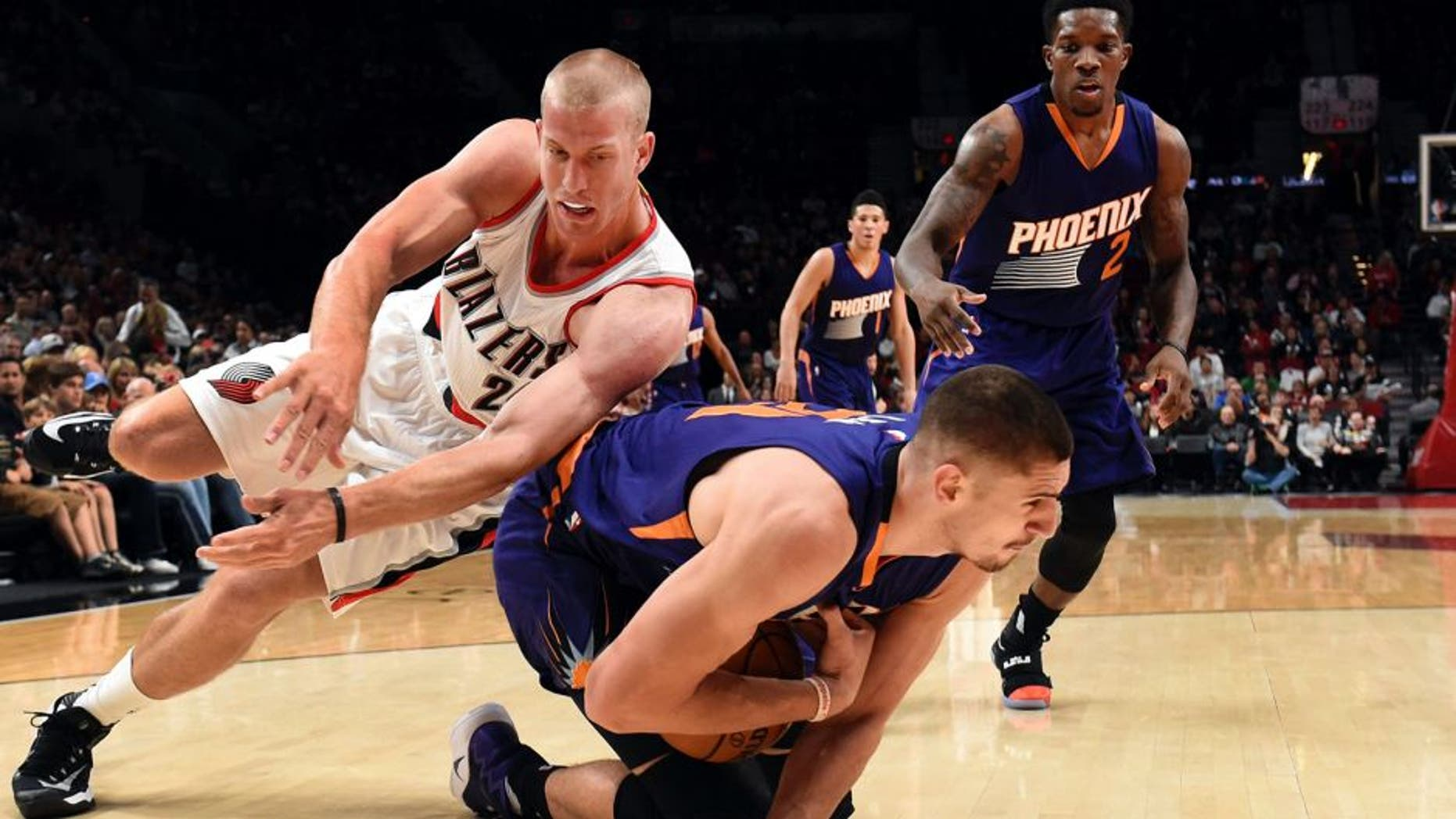 Portland Trail Blazers forward Mason Plumlee dives for the ball with Phoenix Suns center Alex Len during the first quarter of an NBA basketball preseason game in Portland, Ore., Friday, Oct. 7, 2016. (AP Photo/Steve Dykes)