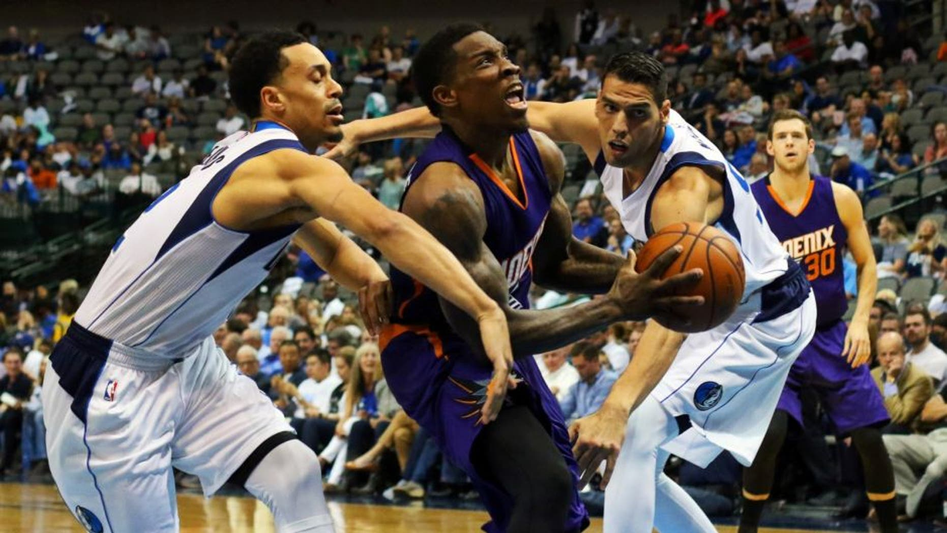 Oct 21, 2015; Dallas, TX, USA; Phoenix Suns guard Eric Bledsoe (2) splits defenders Dallas Mavericks guard John Jenkins (12) and center Salah Mejri (50) during the second half at American Airlines Center. Phoenix won 99-87. Mandatory Credit: Ray Carlin-USA TODAY Sports