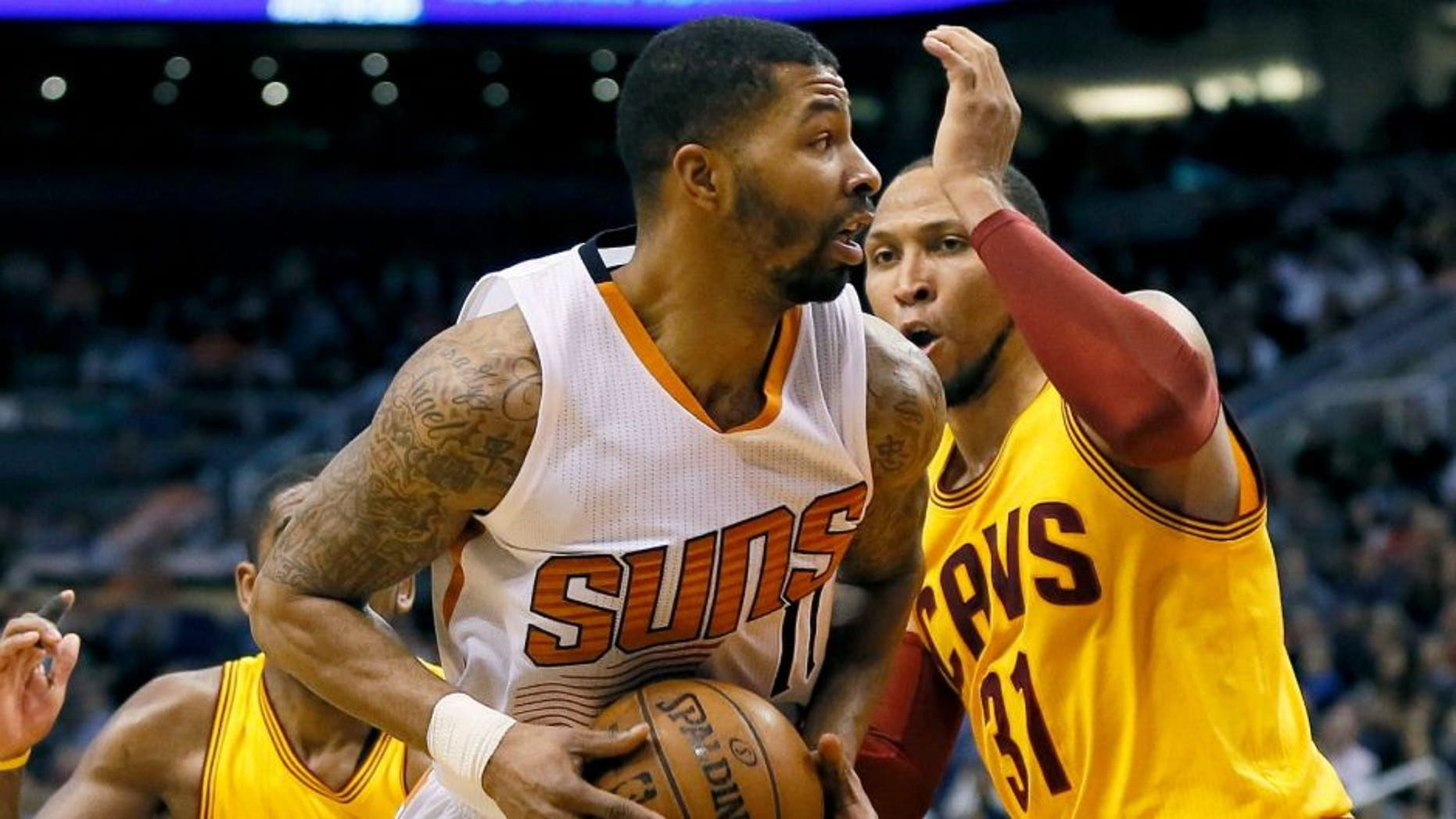 Phoenix Suns' Markieff Morris drives against Cleveland Cavaliers' Shawn Marion during the second half of an NBA basketball game, Tuesday, Jan. 13, 2015, in Phoenix. The Suns won 107-100. (AP Photo/Matt York)