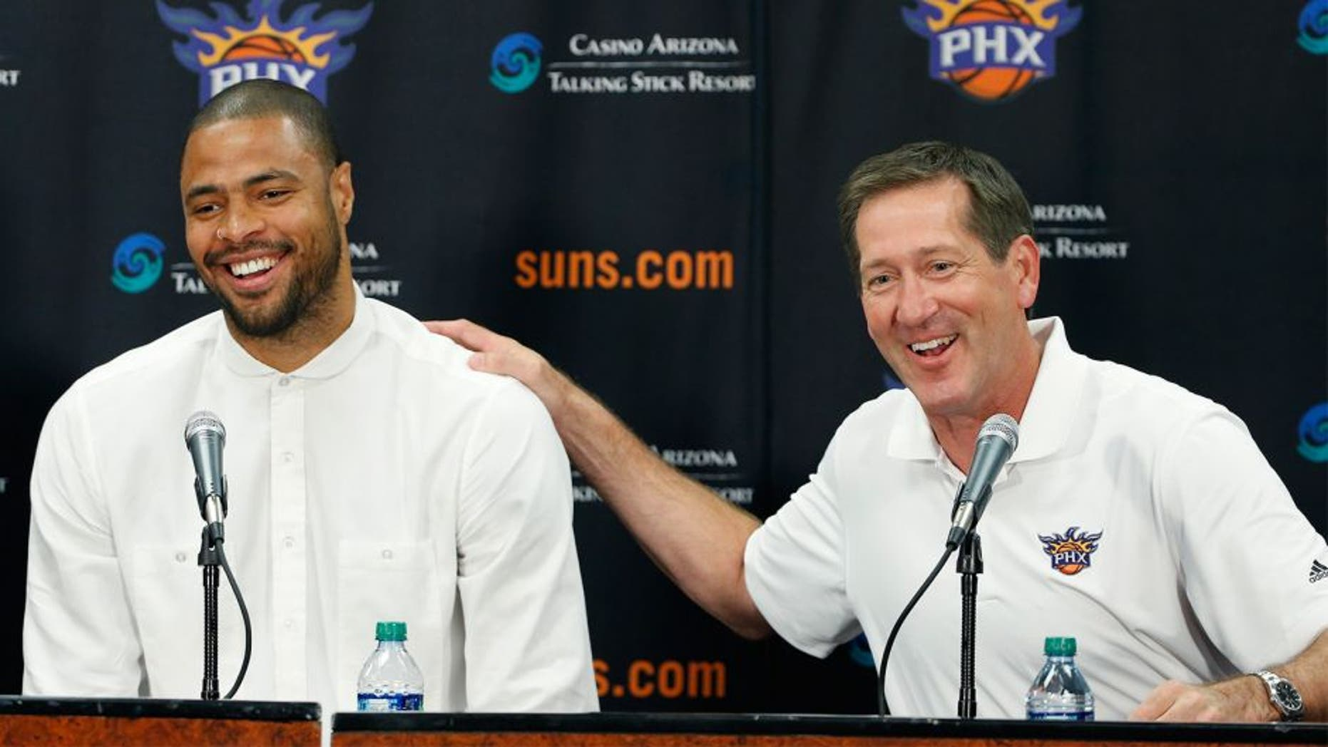 Phoenix Suns' Tyson Chandler, left, the newly signed free agent, laughs along with head coach Jeff Hornacek, right, as Chandler is introduced to the media during a news conference Thursday, July 9, 2015, in Phoenix. (AP Photo/Ross D. Franklin)