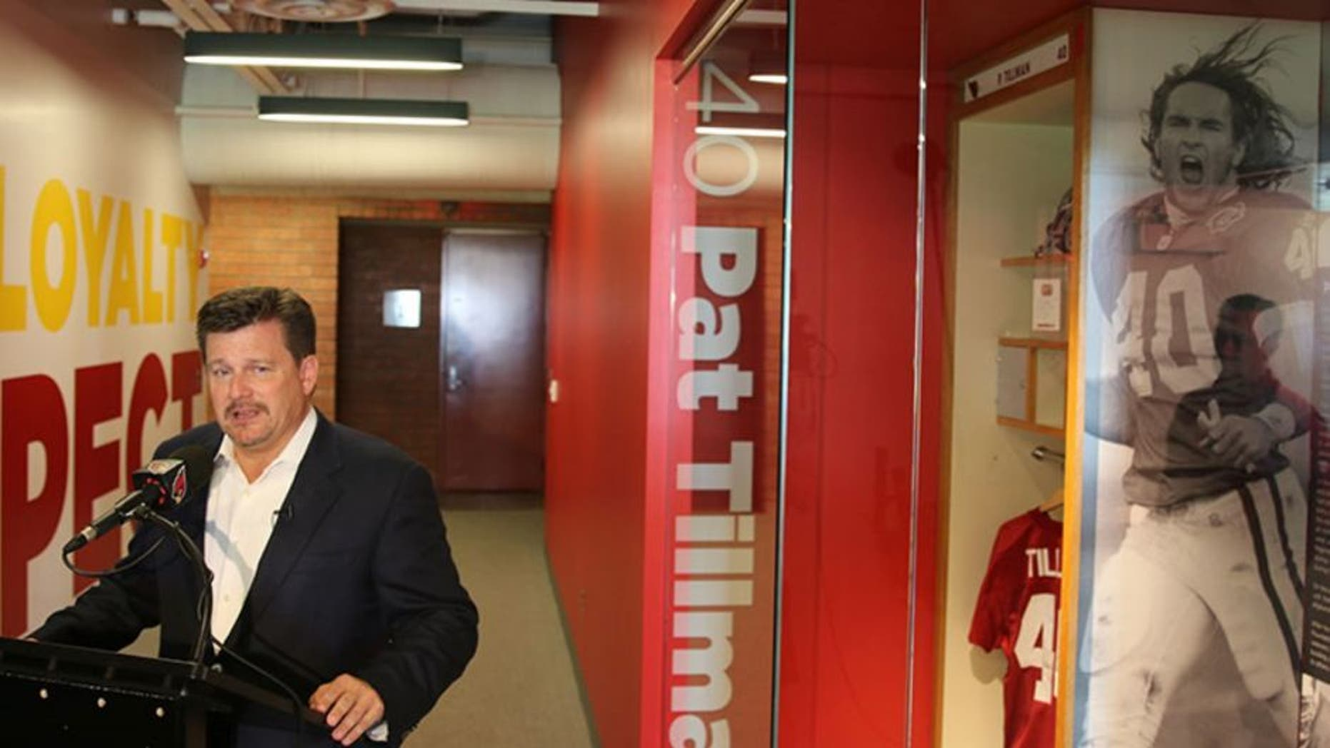 Cardinals president Michael Bidwill talks about the team's training facility renovation while standing next to the Pat Tillman honorary locker.