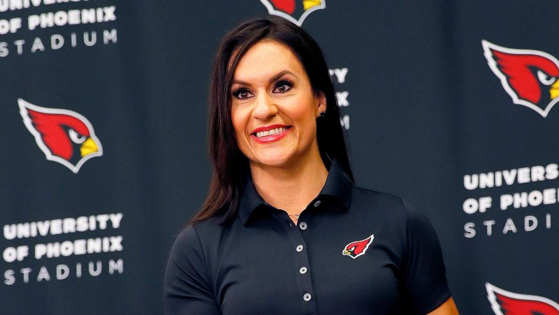Arizona Cardinals training camp football coach Dr. Jen Welter poses for photographers after being introduced, Tuesday, July 28, 2015, at the teams' training facility in Tempe, Ariz. Welter is believed to be the first female to hold a coaching position of any kind in the NFL and will be member of the Cardinals coaching staff throughout training camp and the preseason, working with inside linebackers. (AP Photo/Matt York)