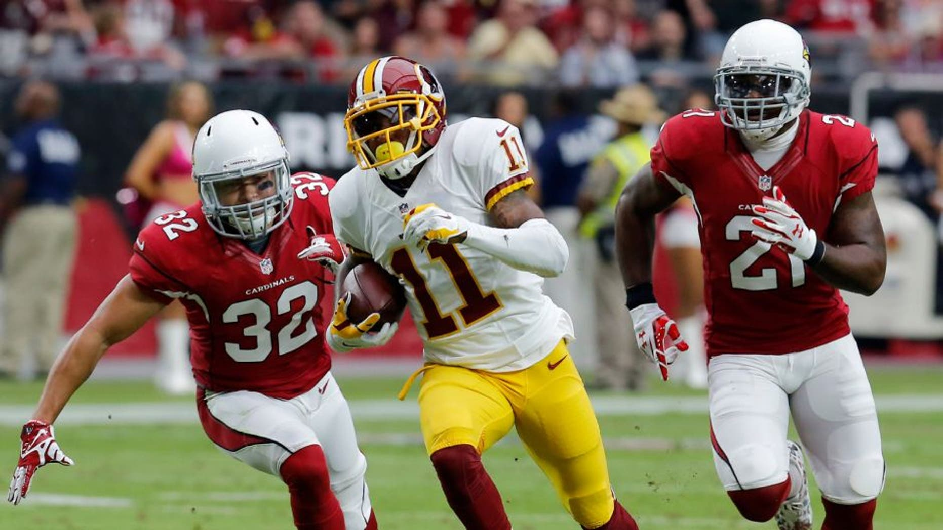 Washington Redskins wide receiver DeSean Jackson (11) runs for a touchdown as Arizona Cardinals free safety Tyrann Mathieu (32) and Patrick Peterson (21) pursue during the first half of an NFL football game, Sunday, Oct. 12, 2014, in Glendale, Ariz.(AP Photo/Rick Scuteri)