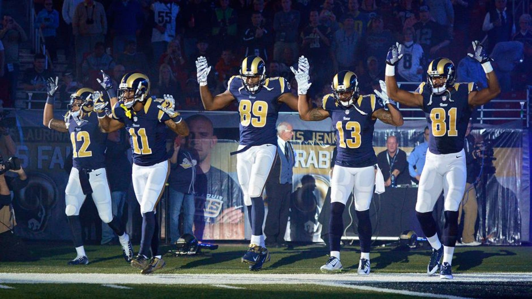 Nov 30, 2014; St. Louis, MO, USA; St. Louis Rams wide receiver Stedman Bailey (12) and wide receiver Tavon Austin (11) and tight end Jared Cook (89) and wide receiver Chris Givens (13) and wide receiver Kenny Britt (81) put their hands up to show support for Michael Brown before a game against the Oakland Raiders at the Edward Jones Dome. Mandatory Credit: Jeff Curry-USA TODAY Sports