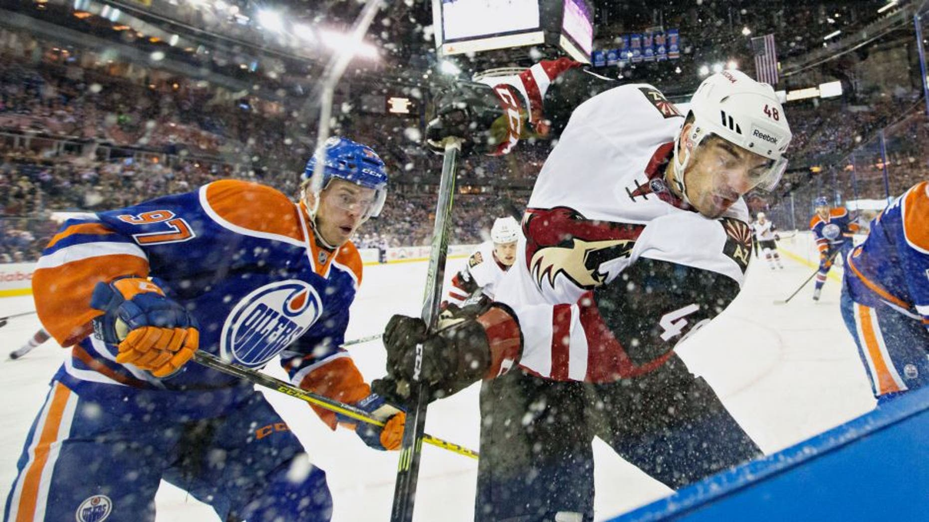 Arizona Coyotes' Jordan Martinook, right, and Edmonton Oilers' Connor McDavid (97) battle in the corner during the first period of a preseason NHL hockey game in Edmonton, Alberta, Tuesday, Sept. 29, 2015. (Jason Franson/The Canadian Press via AP) MANDATORY CREDIT