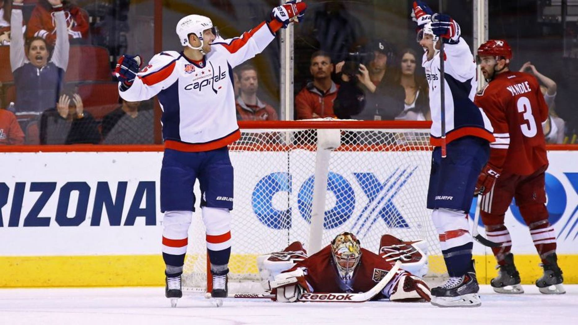 Nov 18, 2014; Glendale, AZ, USA; Washington Capitals right wing Eric Fehr (left) celebrates with right wing Troy Brouwer (right) after scoring the winning goal against Arizona Coyotes goaltender Mike Smith in overtime at Gila River Arena. The Capitals defeated the Coyotes 2-1 in overtime. Mandatory Credit: Mark J. Rebilas-USA TODAY Sports