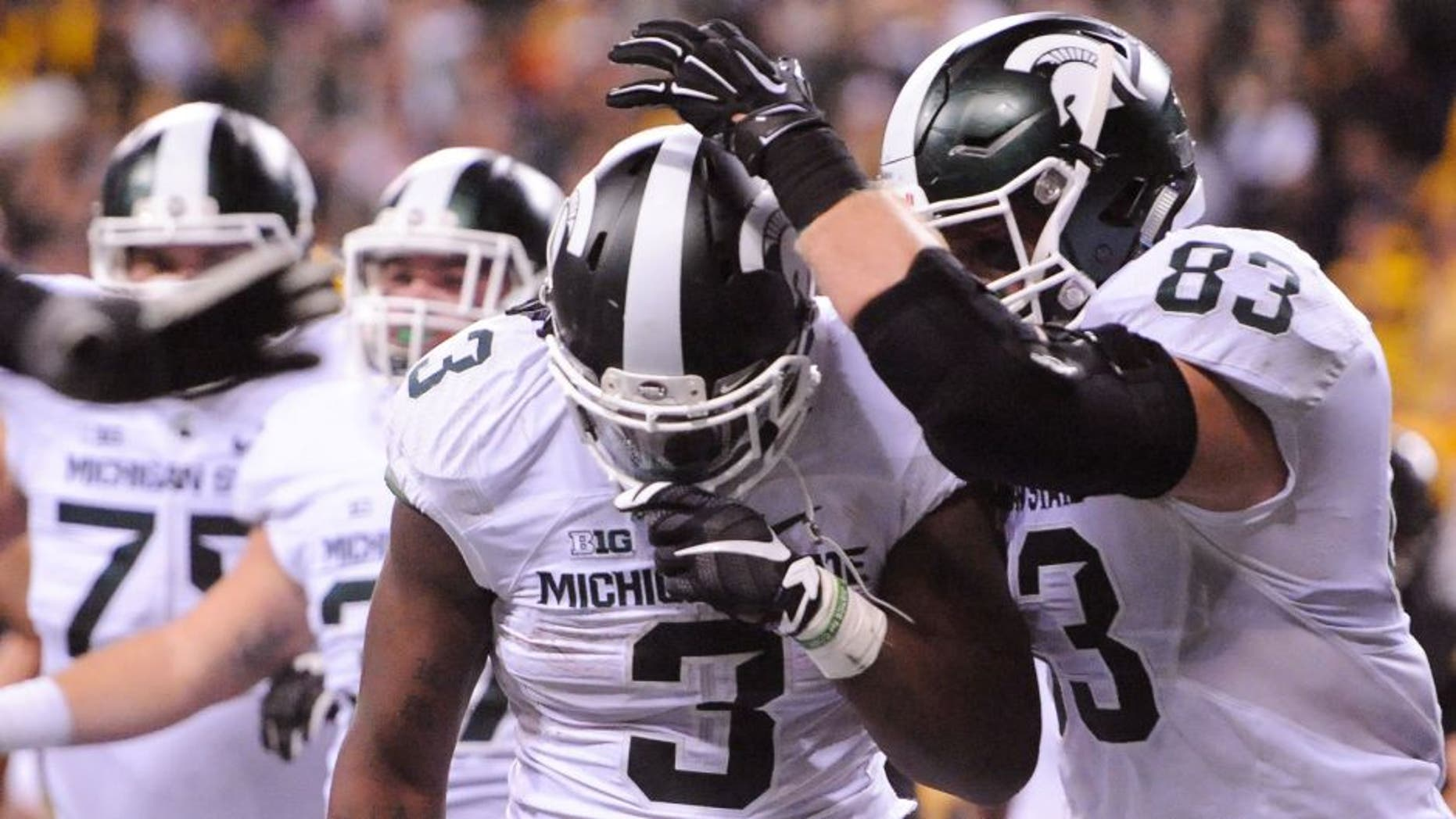 Dec 5, 2015; Indianapolis, IN, USA; Michigan State Spartans running back LJ Scott (3) celebrates the game-winning touchdown with tight end Paul Lang (83) over the Iowa Hawkeyes during the fourth quarter in the Big Ten Conference football championship game at Lucas Oil Stadium. Michigan State won 16-13. Mandatory Credit: Thomas J. Russo-USA TODAY Sports