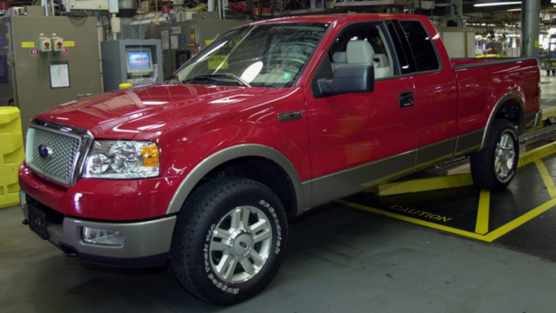FILE - In this June 10, 2003 file photo, the first of Ford's 2004 F-150 trucks waits to roll off the assembly line at the Norfolk, Va., assembly plant. Ford is recalling more than a million pickups trucks because their gas tanks can fall off and cause fires. The recall involves certain 1997 through 2004 Ford F-150 models, as well as some 1997 through 1999 model year F-250 pickups. Also affected are Lincoln Blackwood pickups from the 2002 and 2003 model years. (AP Photo/Gary C. Knapp, File)