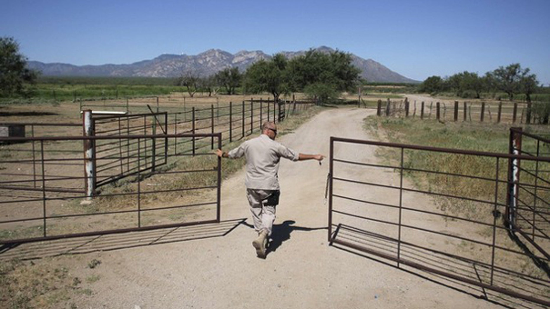 A Border Patrol agent opens a gate leading to a dirt road as he searches for illegal immigrants in the dessert of Pima County, Ariz., Aug. 17, 2009. (Reuters Photo)