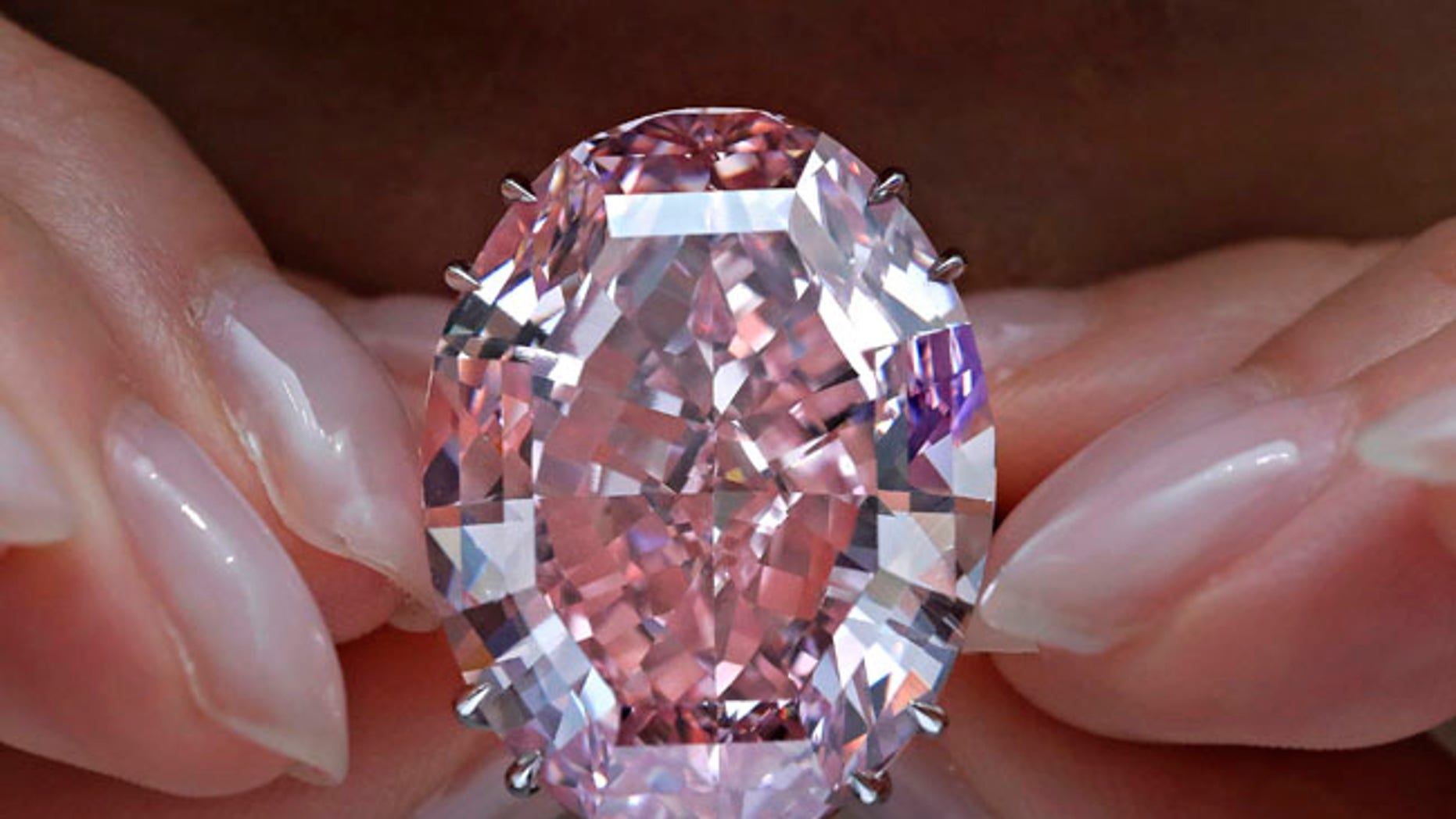 "The ""Pink Star"" diamond, the most valuable cut diamond ever offered at auction, is displayed by a model at a Sotheby's auction room in Hong Kong. The stunning 59.6 carat diamond has sold for $71.2 million at auction, a record price."