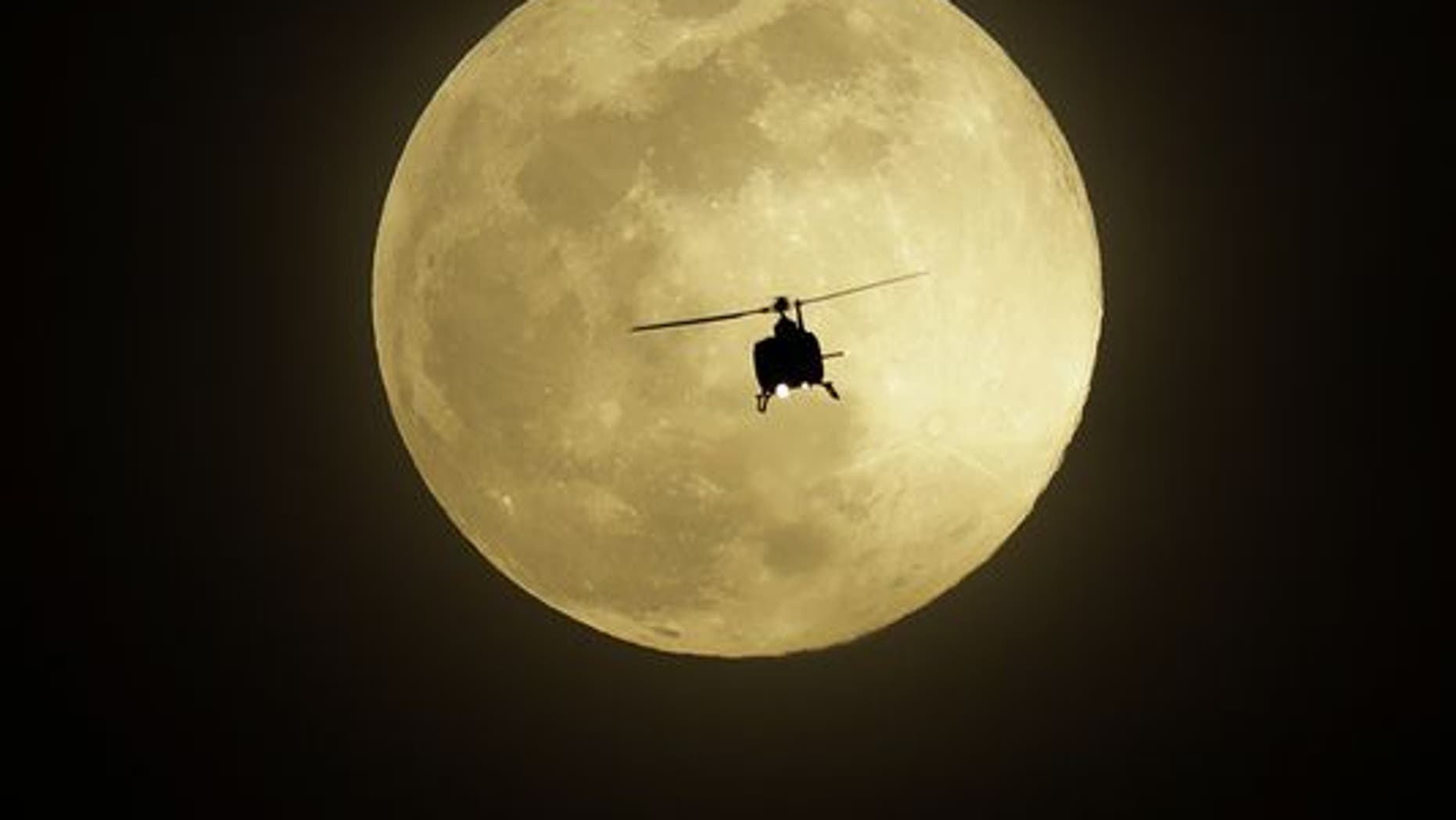 A Helicopter Flies In Front Of The Pink Moon On Monday Las Vegas