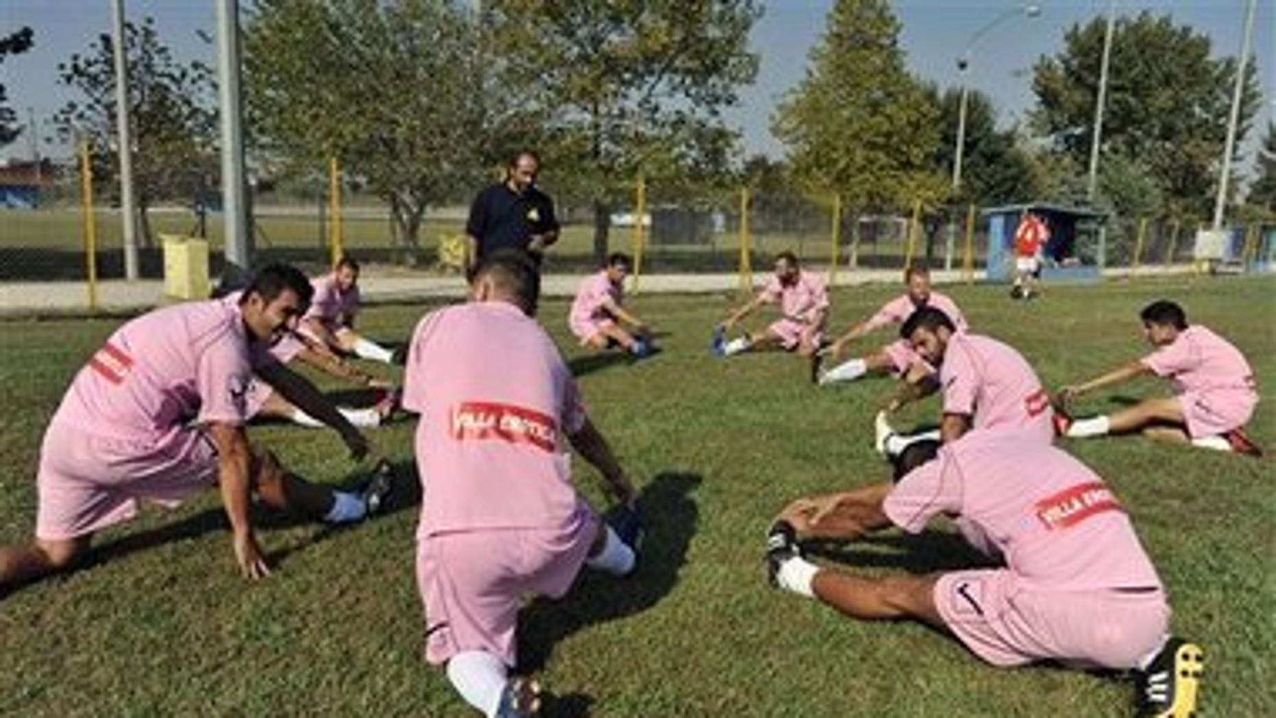 Voukefalas players, a small amateur soccer club, warm up before a local championship match in the city of Larissa, central Greece. A cash-strapped Greek soccer team has found a new way to pay the bills, with help from the world's oldest profession. Players are wearing bright pink practice jerseys emblazoned with the logos of the Villa Erotica and Soulaâs House of History, a pair of pastel-colored bordellos recruited to sponsor the team after drastic government spending cuts left the country's sports organizations facing ruin.