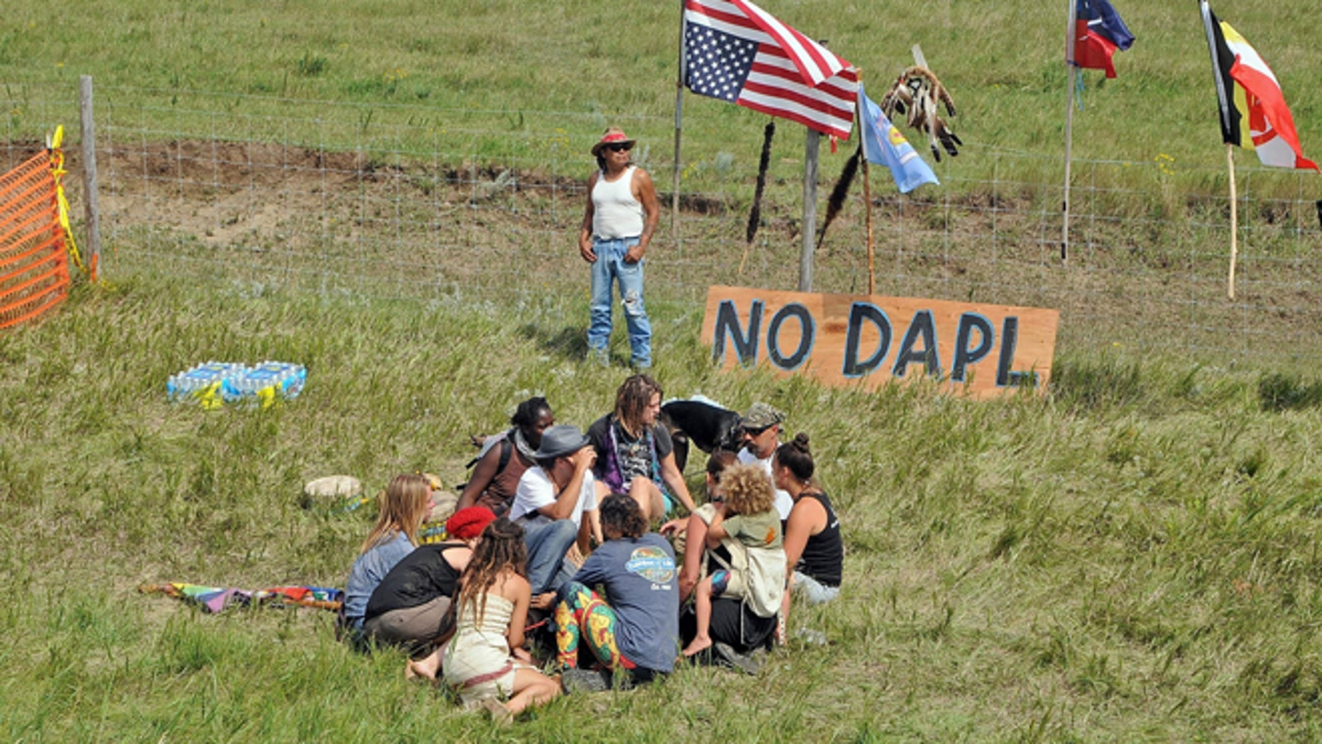 Bill Left Hand, of McLaughlin, South Dakota, stands next to a sign at the site of a protest Friday, Aug. 12, 2016, against construction of the Dakota Access Pipeline that will cross the Missouri River in Morton County.