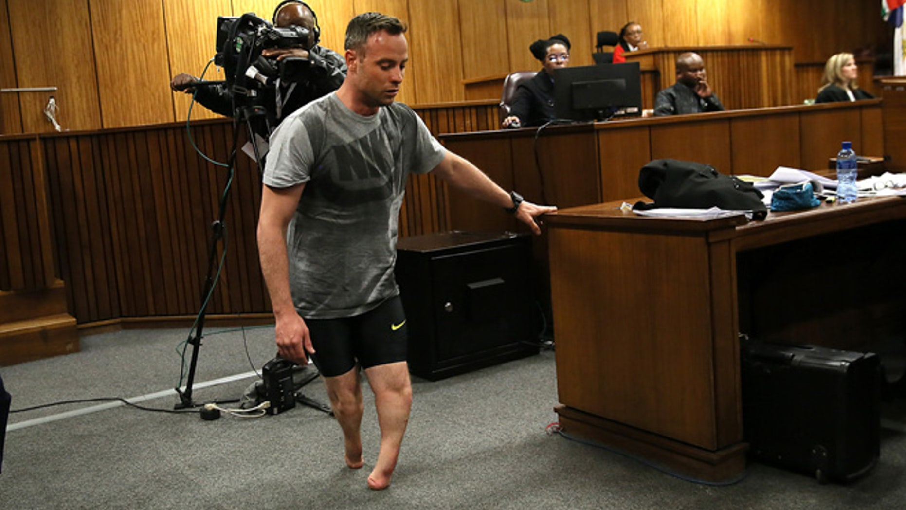 Oscar Pistorius walks on his stumps during argument in mitigation of sentence by his defense attorney Barry Roux in the High Court in Pretoria, South Africa, Wednesday, June 15, 2016. An appeals court found Pistorius guilty of murder and not a lesser charge of culpable homicide for the shooting death of his girlfriend Reeva Steenkamp.  (AP Photo/Alon Skuy, Pool via AP)