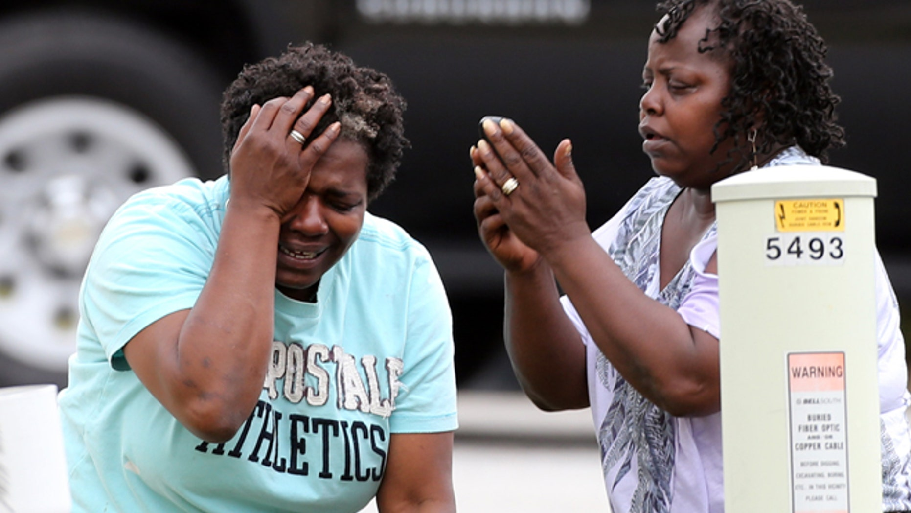 April 24: After finding out that a two-year-old had been killed by his South Fulton family's pit bull, a relative grieves and a family friend makes a call in an unincorporated area in south Fulton County near Union City, Ga.