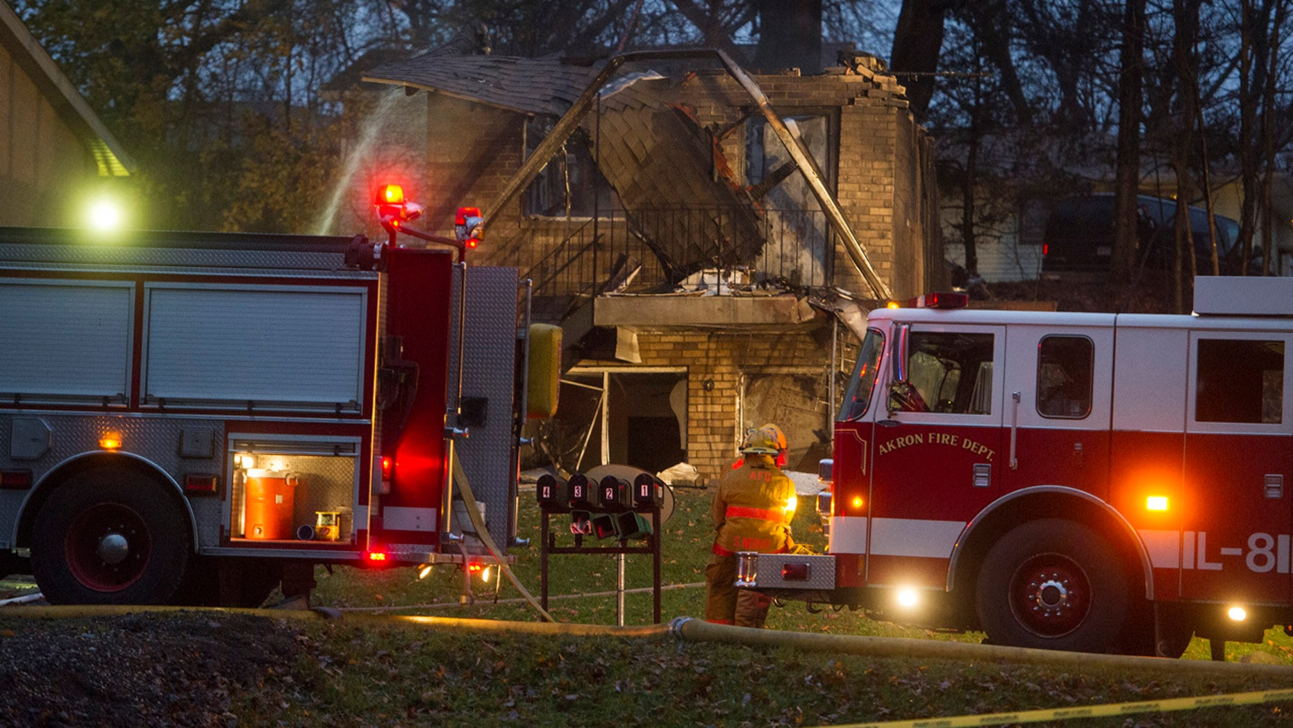 In this Nov. 10, 2015, file photo, firefighters work at the scene where a small business jet crashed into an apartment building in Akron, Ohio.