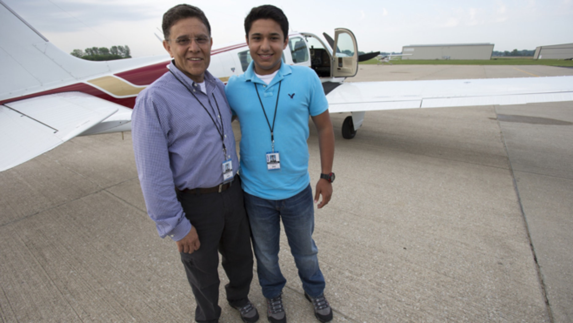 June 19, 2014: Babar Suleman and son Haris Suleman, 17, stand next to their plane at an airport in Greenwood, Ind. before taking off for an around-the-world flight. (AP/The Indianapolis Star)