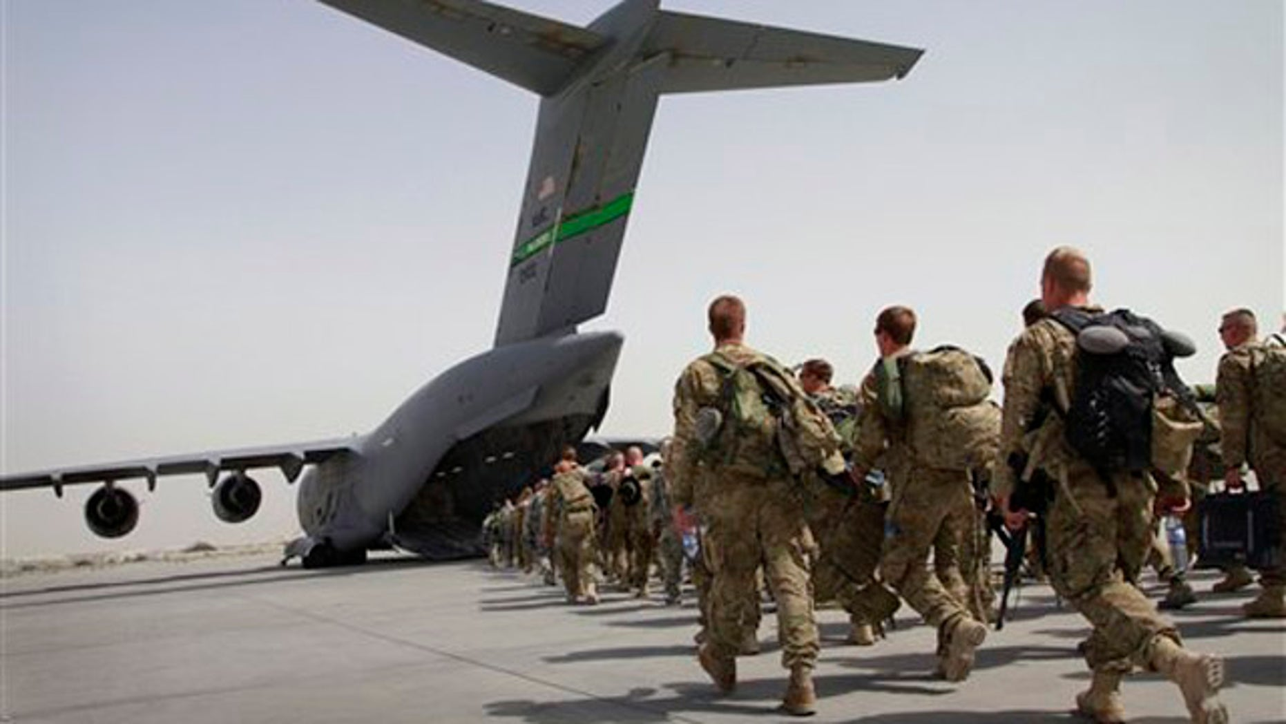 U.S. soldiers walk to board a U.S. military plane, as they leave Afghanistan at the U.S. base in Bagram on July 14.