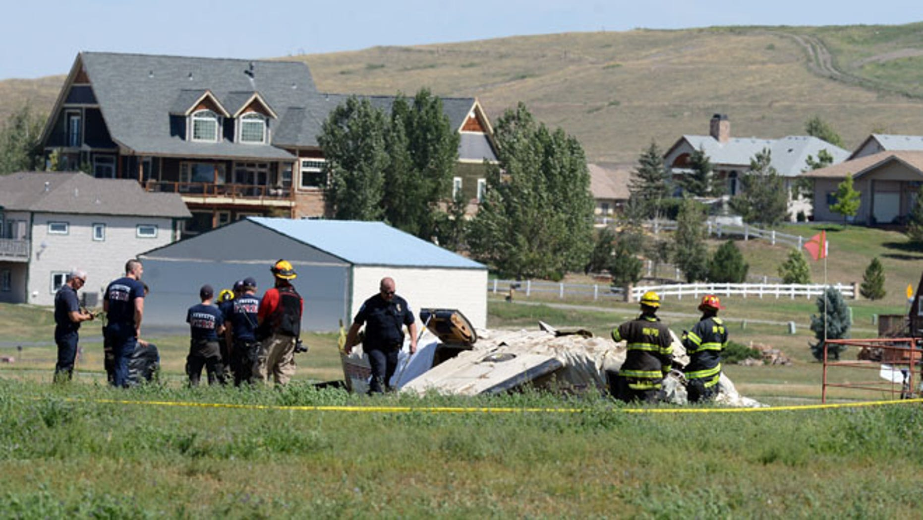 Aug 31, 2014: Police and firefighters work on the scene where three people were killed and two others injured after an airplane crashed in a field northwest of the main runway at Erie Municipal Airport while coming in for a landing in Erie, Colo.