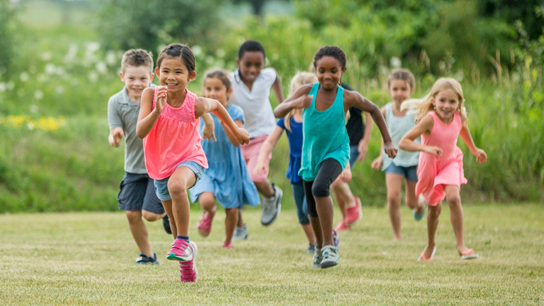 A multi-ethnic group of elementary age children are playing together outside at recess. They are chasing each other and are playing tag.