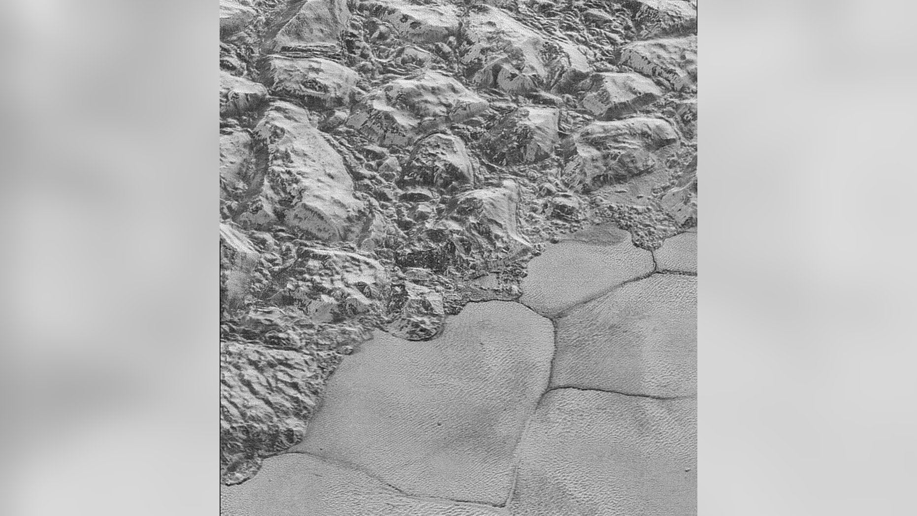 This photo taken by NASA's New Horizons spacecraft during its July 2015 flyby of Pluto shows the mountain range on the edge of the dwarf planet's Sputnik Planitia ice plain. Dune formations are clearly visible in the bottom half of the picture.