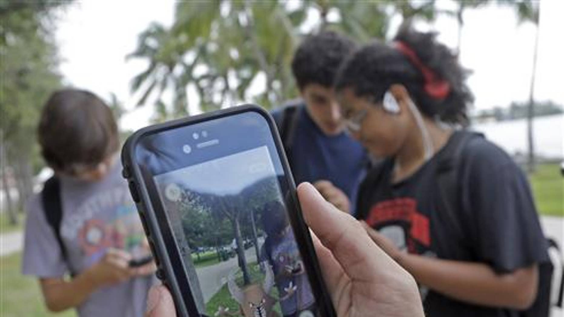 "Pinsir, a Pokemon, is found by a group of Pokemon Go players at Bayfront Park in downtown Miami on July 12, 2016, as the ""Pokemon Go"" craze has sent legions of players hiking around cities and battling with ""pocket monsters"" on their smartphones. (AP Photo/Alan Diaz)"