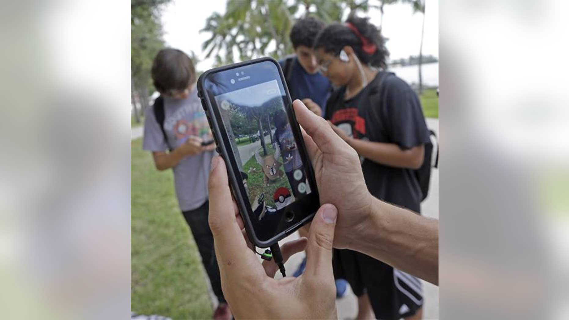 """Pinsir, a Pokemon, is found by a group of Pokemon Go players at Bayfront Park in downtown Miami on July 12, 2016, as the """"Pokemon Go"""" craze has sent legions of players hiking around cities and battling with """"pocket monsters"""" on their smartphones. (AP Photo/Alan Diaz)"""
