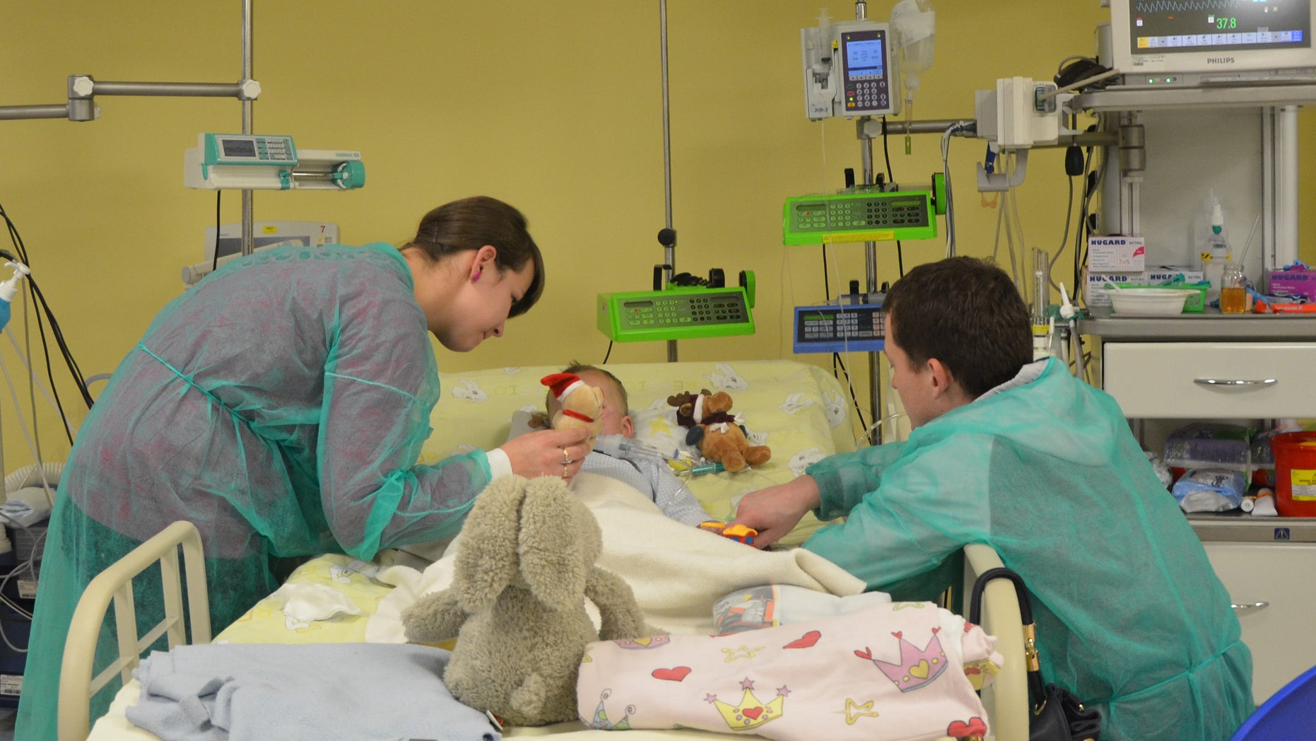 In this photo taken by Magdalena Oberc, the spokeswoman of the childrens hospital in Krakow, Poland, on Thursday, Dec. 4, 2014, a 2-year-and-4-months-old Adam is seen with his mother Paulina, his father Mateusz and a teddy bear, just a few days after he was brought to the hospital with his temperature at only 12.7 C (55 F) and his heart beating once every few dozen seconds after being found outdoors in sub-freezing temperature on Sunday morning with almost no clothes on. Dr. Janusz Skalski, a heart surgeon at the hospital, said its a miracle that the boy is showing no negative signs from the hours that he spent in such low temperature. (AP Photo/Magdalena Oberc, Krakow Childrens Hospital spokeswoman)