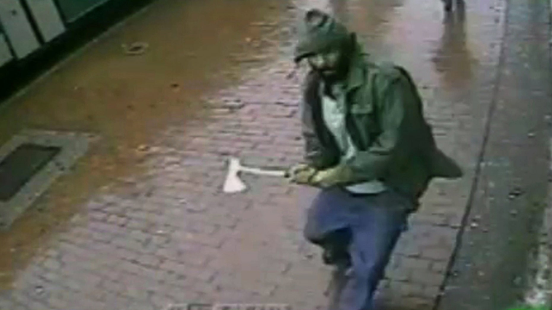 Oct. 23, 2014: In this frame grab taken from video provided by the New York Police Department, an unidentified man approaches New York City police officers with a hatchet