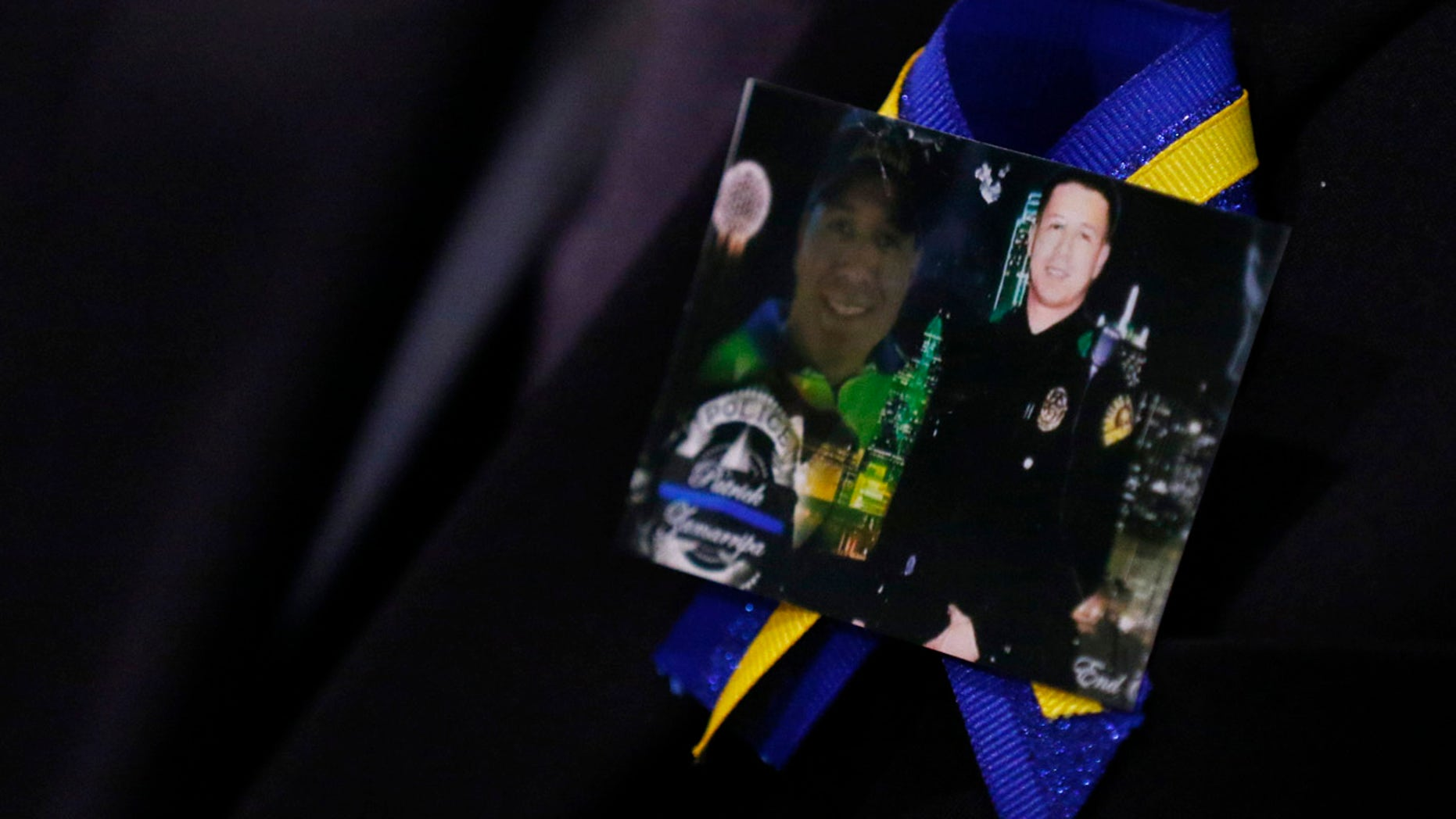 July 16, 2016: A family member wears a ribbon with photos of Patrick Zamarripa during a funeral service for the Dallas police officer