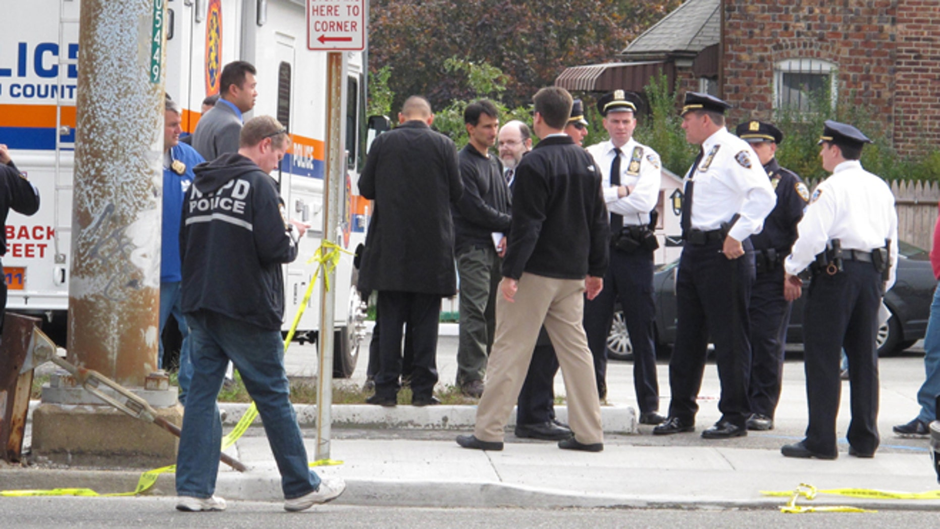 Oct. 24, 2012: Police officers investigate at the scene of a shooting in Bellerose Terrace, N.Y.. A police officer on New Yorks Long Island and another person were killed after shooting erupted Tuesday morning during what a witness described as a routine traffic stop at the New York City limits on Long Island.