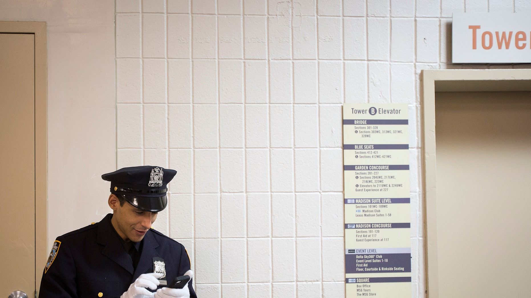 File photo - A New York Police Department graduate video chats on his smartphone backstage before his induction ceremony at Madison Square Garden in New York, December 27, 2013. (REUTERS/Carlo Allegri)