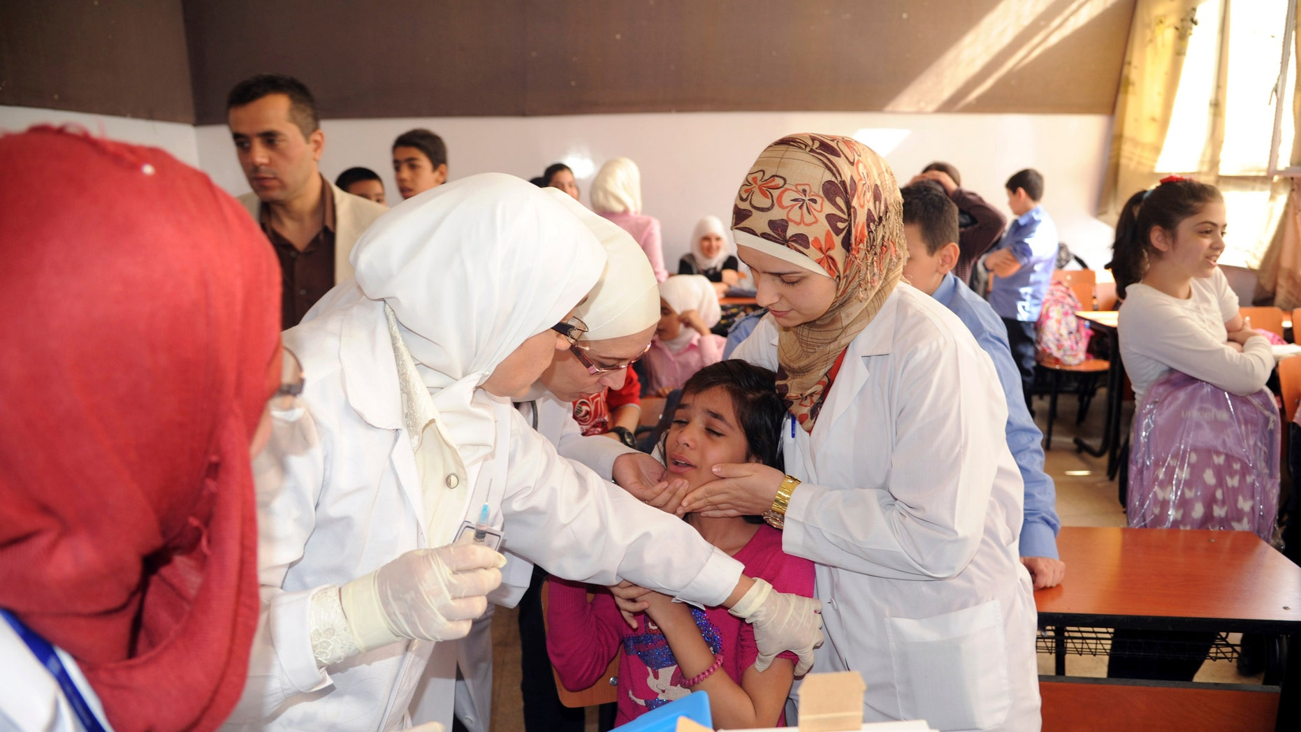 Syrian health workers administer polio vaccination to a girl at a school  in Damascus. (REUTERS/SANA/Handout via Reuters)