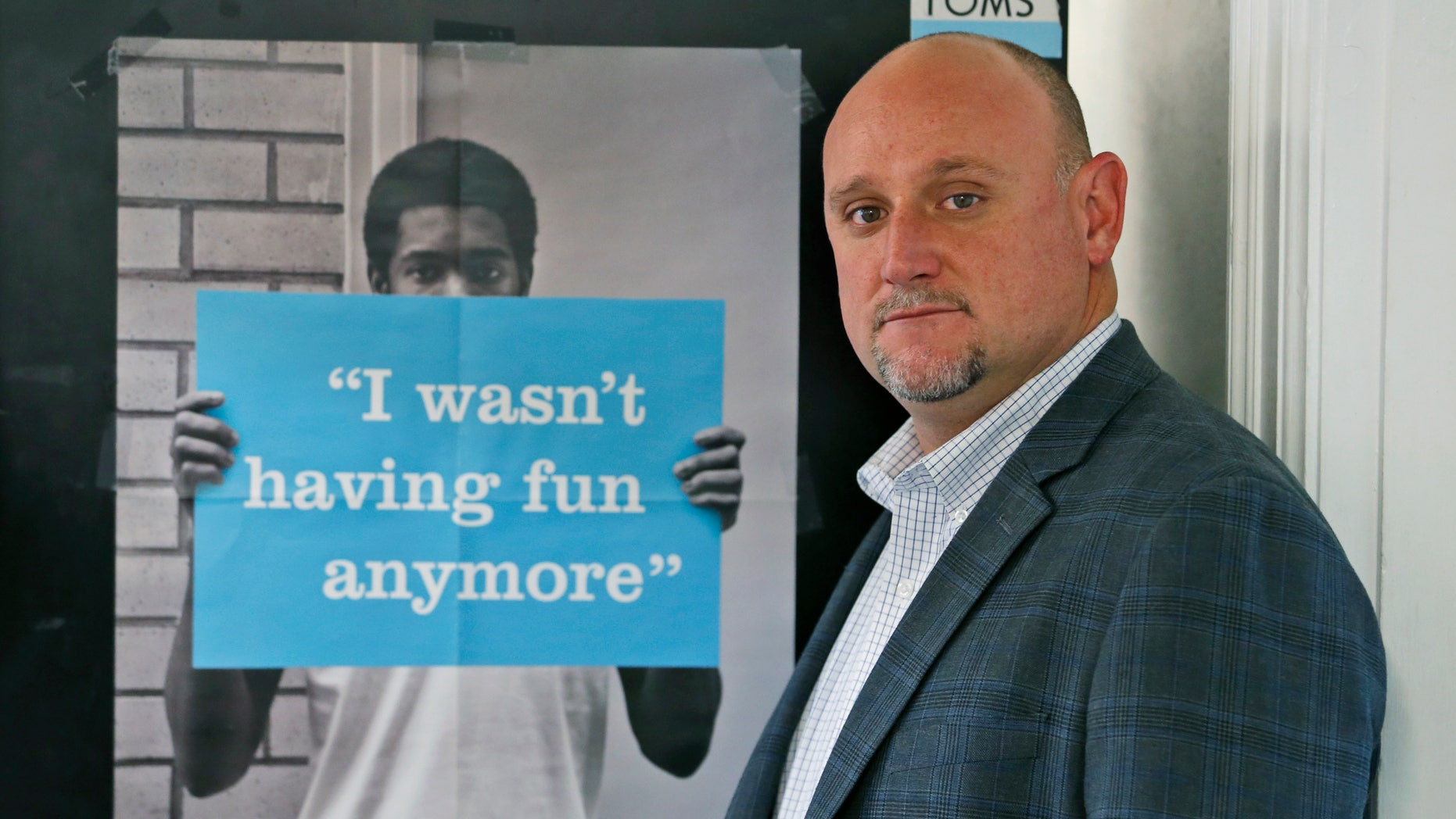 In this Monday, Dec. 5, 2016, photo, David Rook, operations manager for the McShin Foundation, poses next to a poster in the foundation's offices in Richmond, Va.