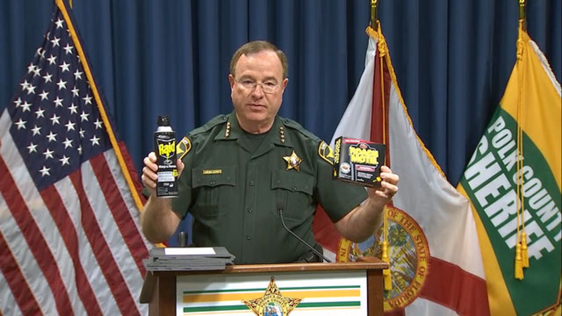 Polk County Sheriff Grady Judd holds roach-killing chemicals as he addresses the media Tuesday.