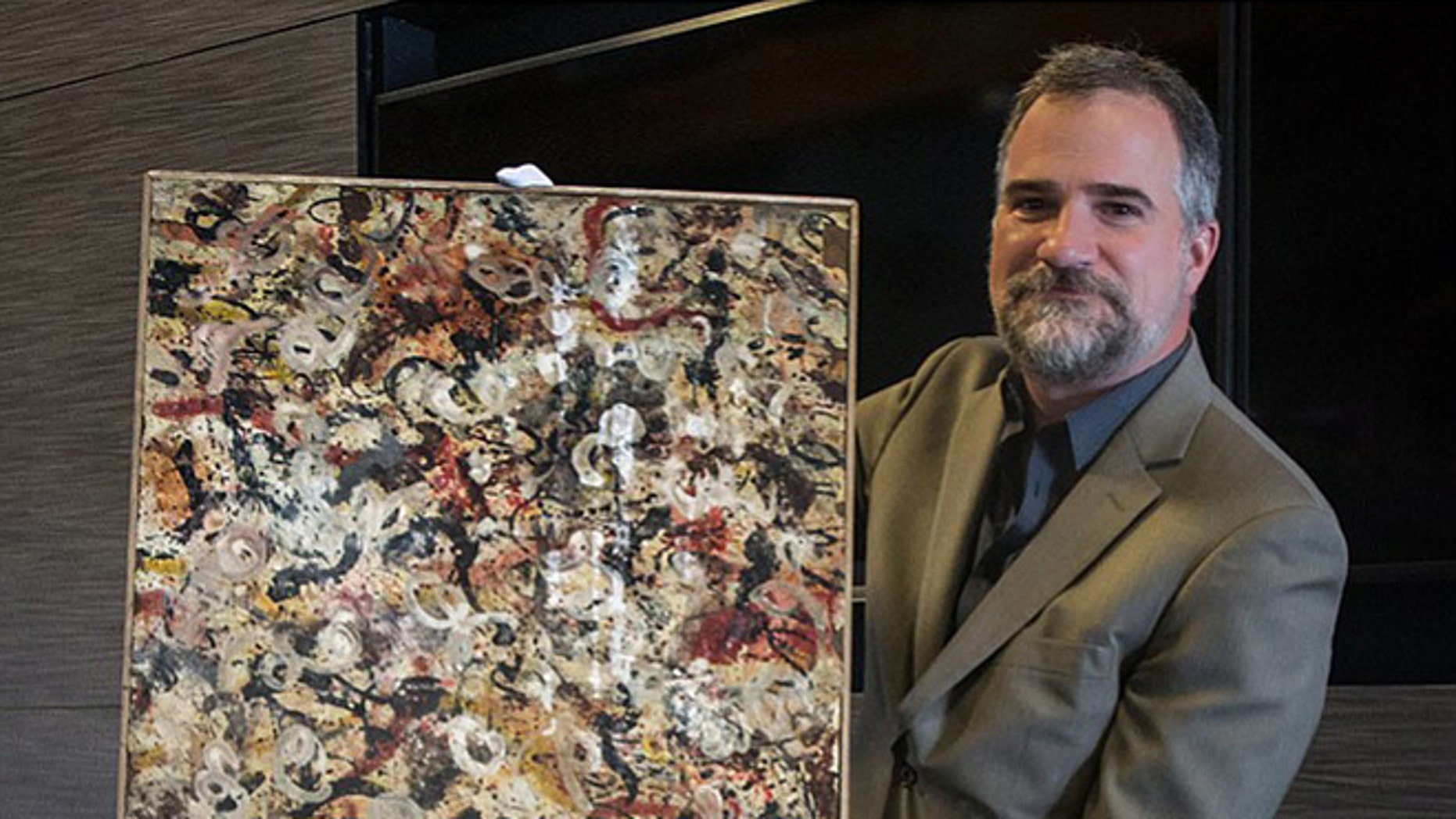 Auctioneer Josh Levine holds a painting that he believes is an original Jackson Pollock and that will go up for auction June 20.