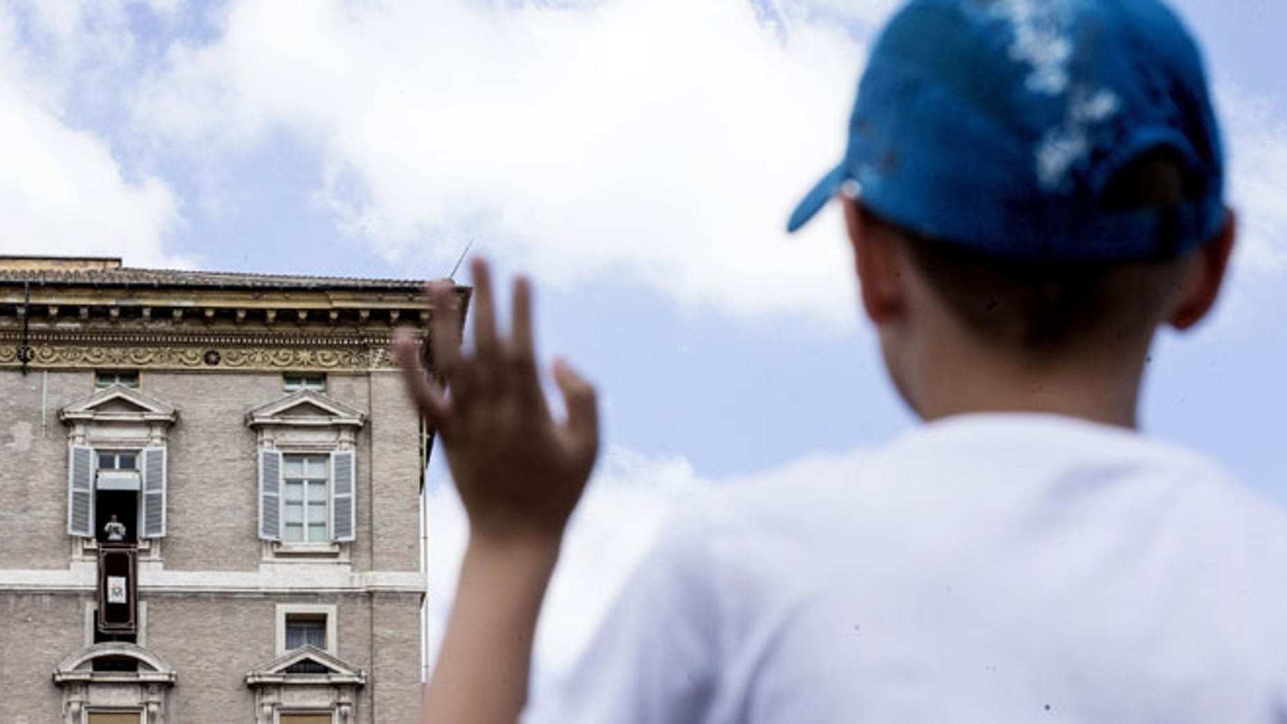 A young boy waves as Pope Francis delivers his message from his studio window overlooking St. Peter's Square during the Sunday Angelus prayer, at the Vatican, Sunday, Aug. 14, 2016. (Angelo Carconi/ANSA via AP)