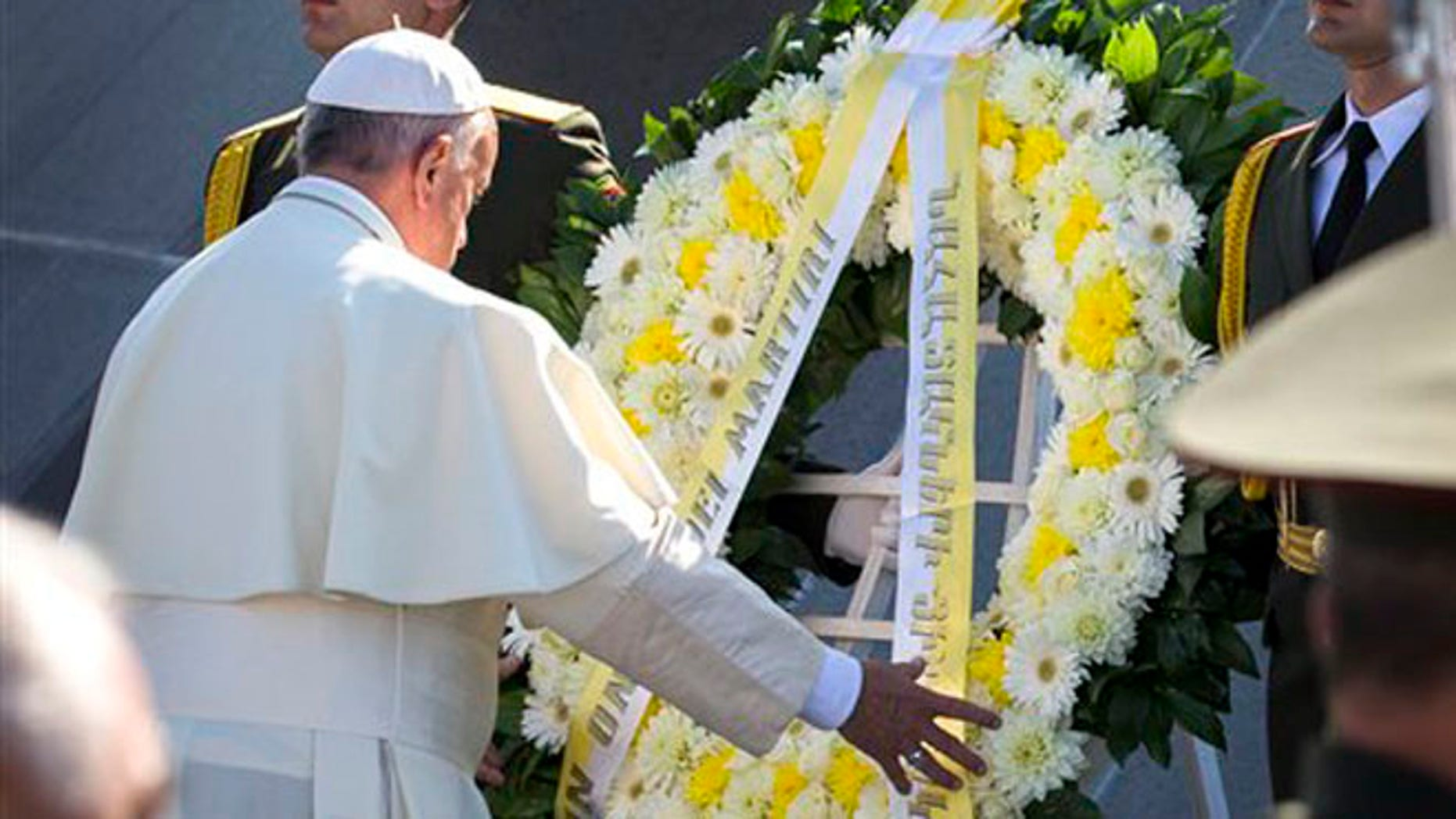 Pope Francis, left, attends a ceremony at a memorial to Armenians killed by the Ottoman Turks in Yerevan, Armenia, Saturday, June 25, 2016. Francis used another opportunity to pay respects to the victims of the slaughter when he visits Armenia's genocide memorial. (AP Photo/Alexander Zemlianichenko)