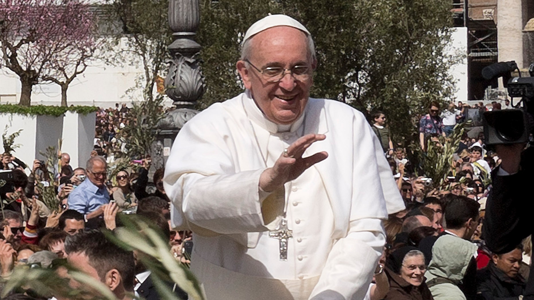 March 24, 2013: Pope Francis waves at a cheering crowd as he wades through St. Peter's Square at the Vatican.