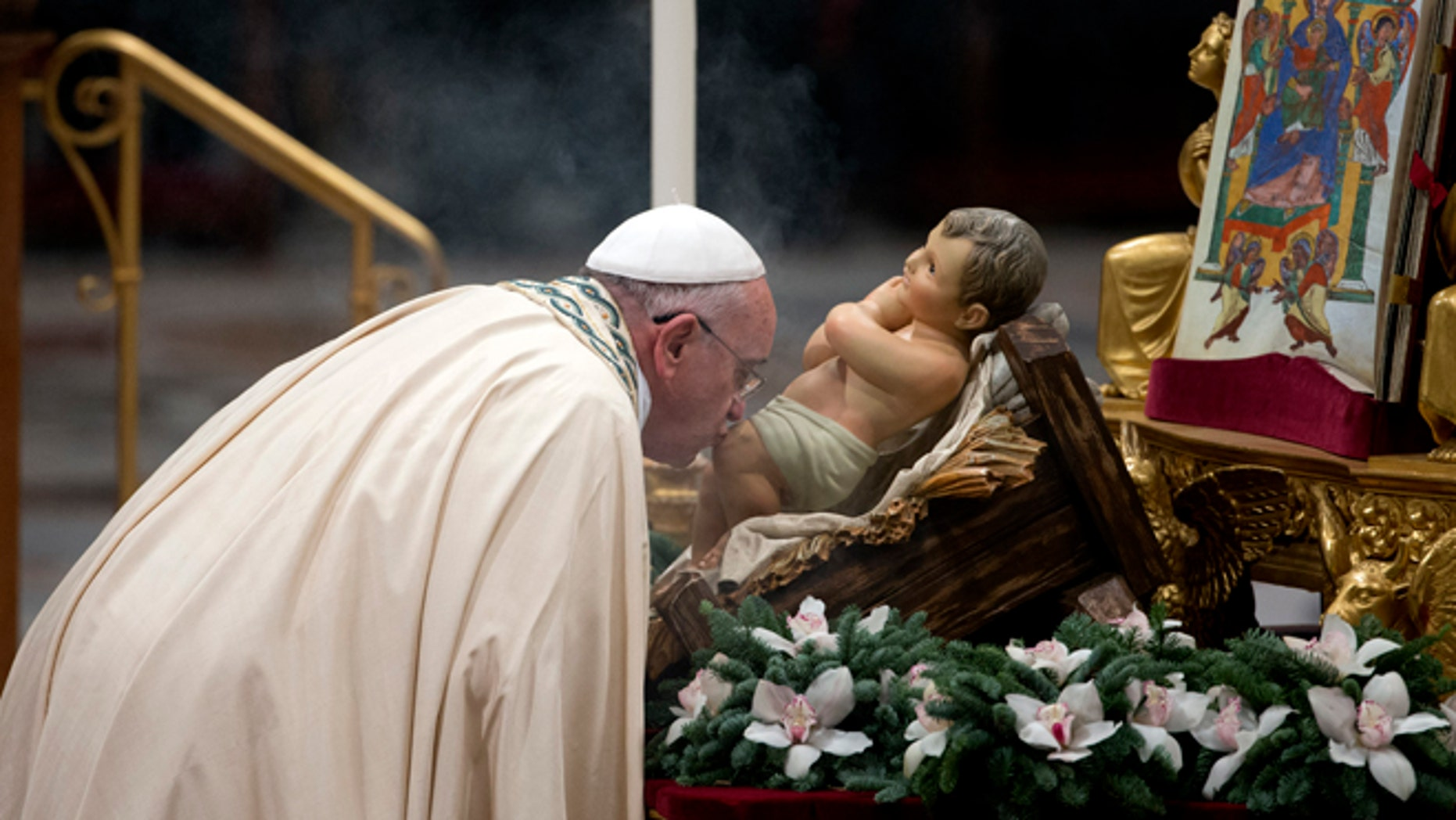 Dec. 31, 2014: Pope Francis kisses a statue of the baby Jesus as he arrives to celebrate the new year's eve vespers Mass in St. Peter's Basilica at the Vatican. (AP)