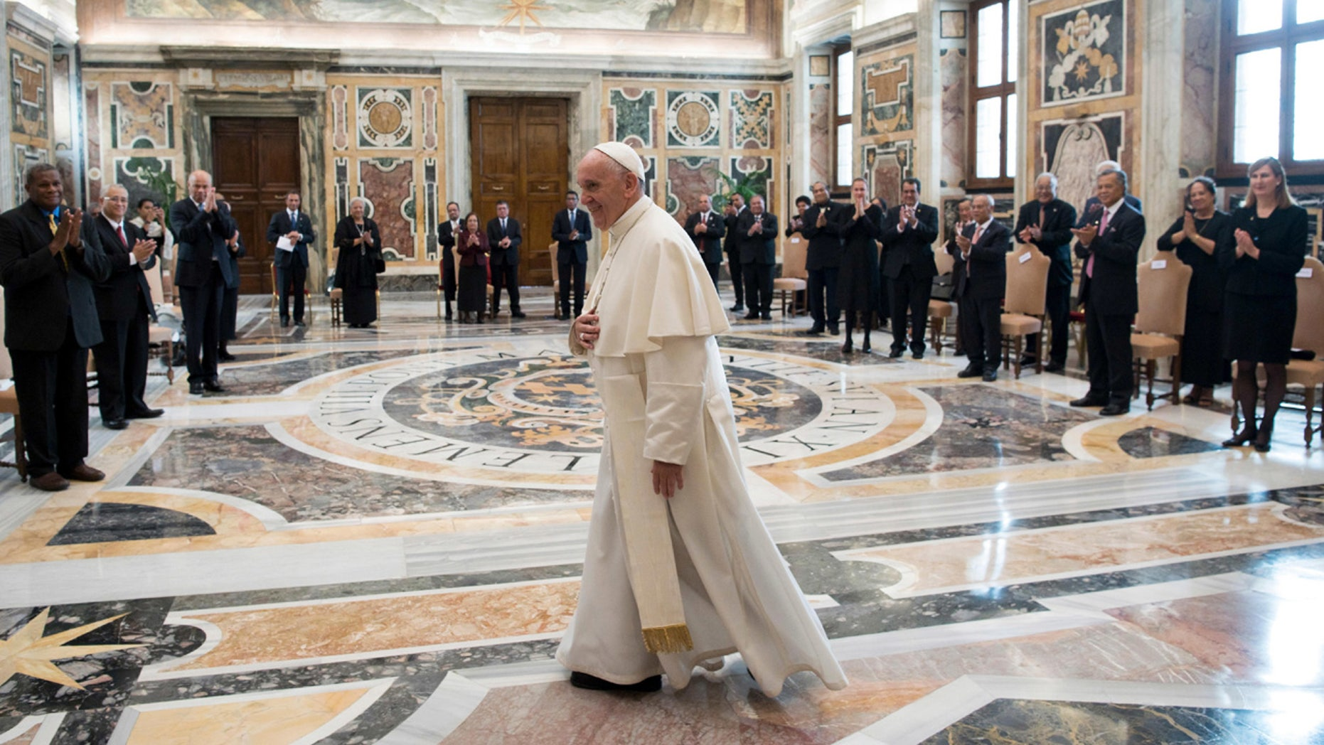 Pope Francis walks in the Clementine Hall after meeting with a delegation of Pacific leaders to discuss climate issues at the Vatican.
