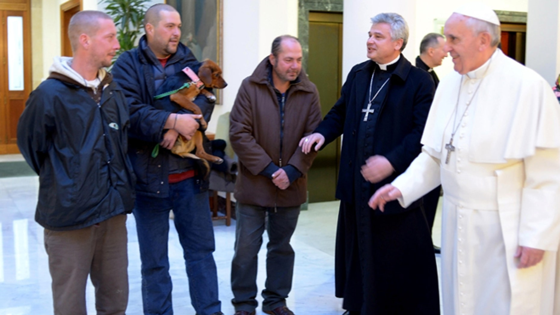Dec. 17, 2013: In this picture provided by the Vatican newspaper L'Osservatore Romano, Pope Francis, right, is flanked by Vatican Almoner Archbishop Konrad Krajewski as he welcomes four men at the Vatican.