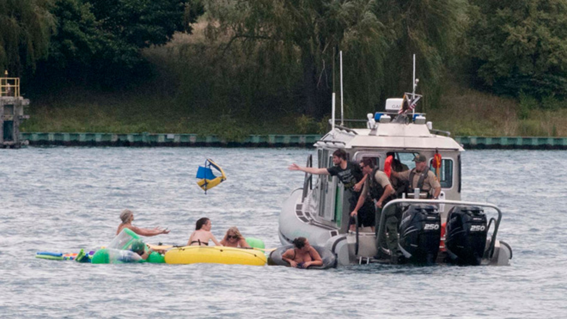 A Customs and Border Protection boat helps floaters during Float Down on the St. Clair River in Port Huron, Mich., Sunday, Aug. 21, 2016. The west winds blew most boaters toward the Canada shore and they had to be pulled back to the U.S.