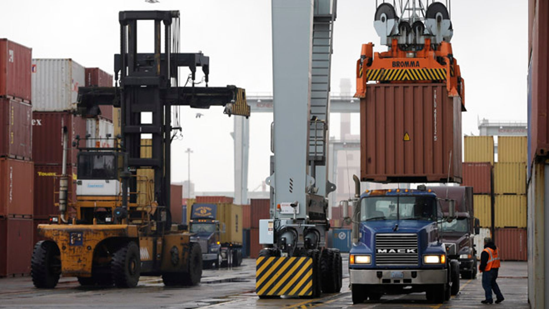 Dec. 18, 2012: A truck driver watches as a freight container, right, is lowered at the Port of Boston.