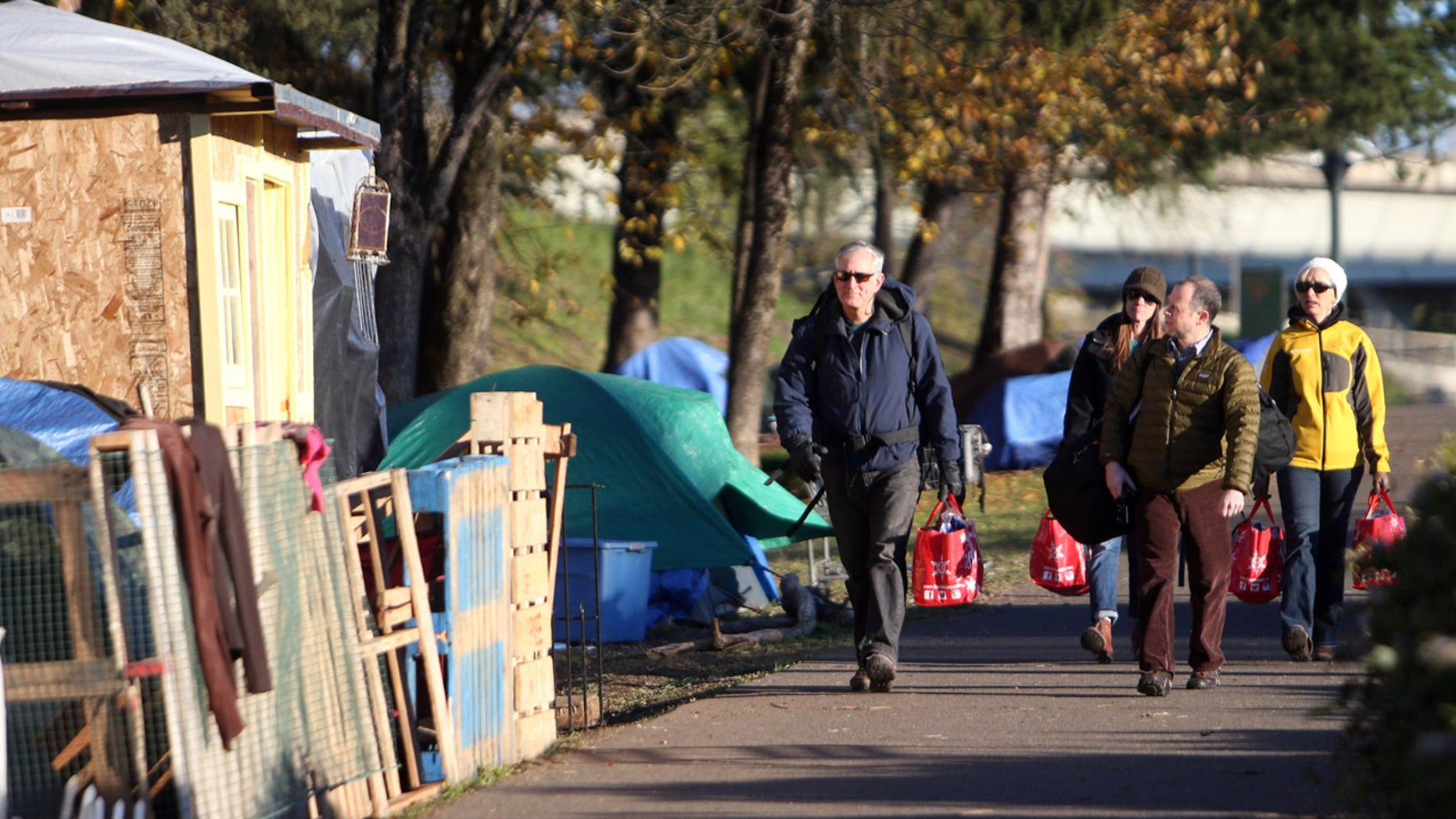 Nov. 27, 2015: Portland Mayor Charlie Hales, left, and his chief of staff Josh Alpert visit the Hazelnut Groove homeless camp in North Portland, Ore.