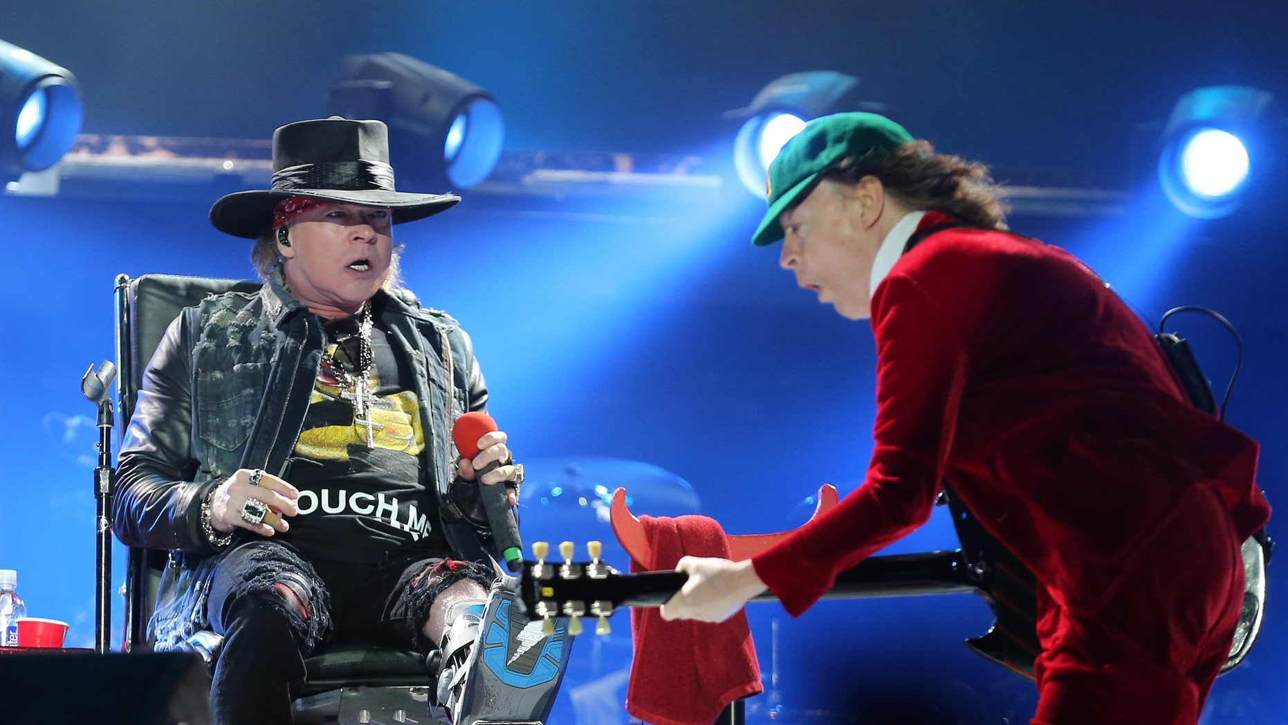 Guns N' Roses singer Axl Rose, left, watches AC/DC lead guitar player Angus Young perform during the concert of Australian rock band AC/DC in Lisbon Saturday night, May 7, 2016.